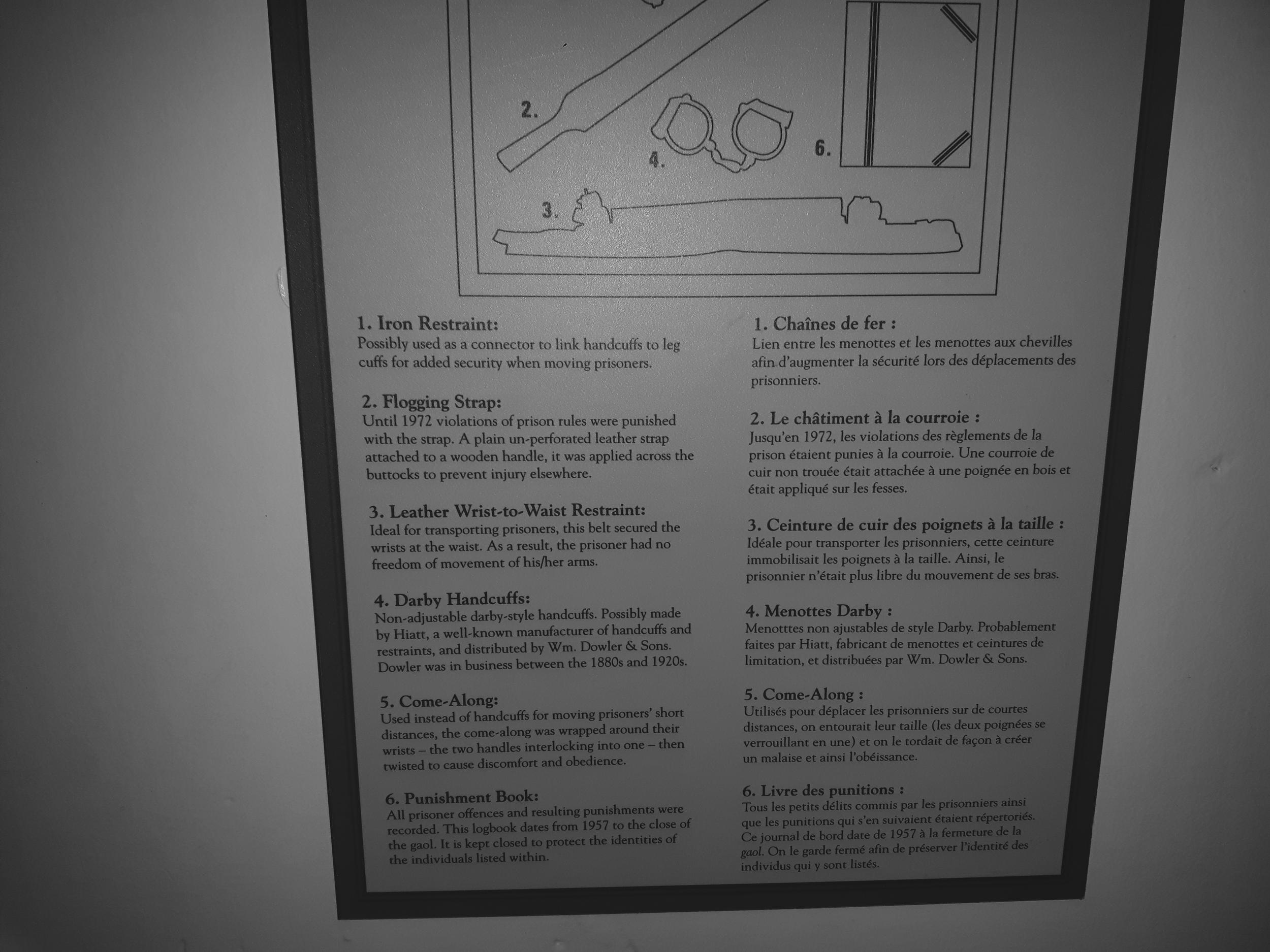 Museum plaque about torture and restraints.