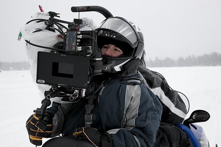 Kristina, shooting on the back of a snowmobile.