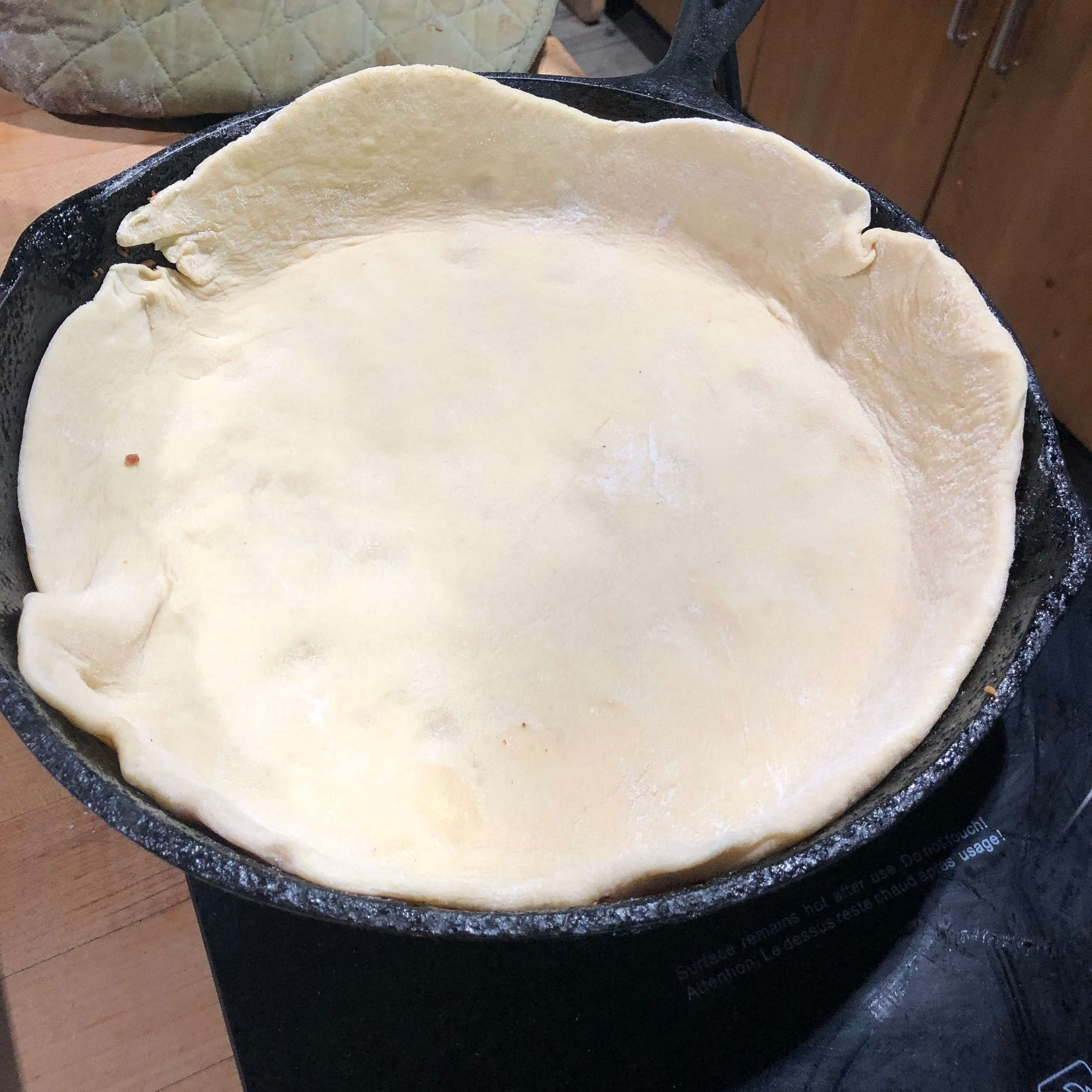 Pizza crust sizzling in fat from the sausage
