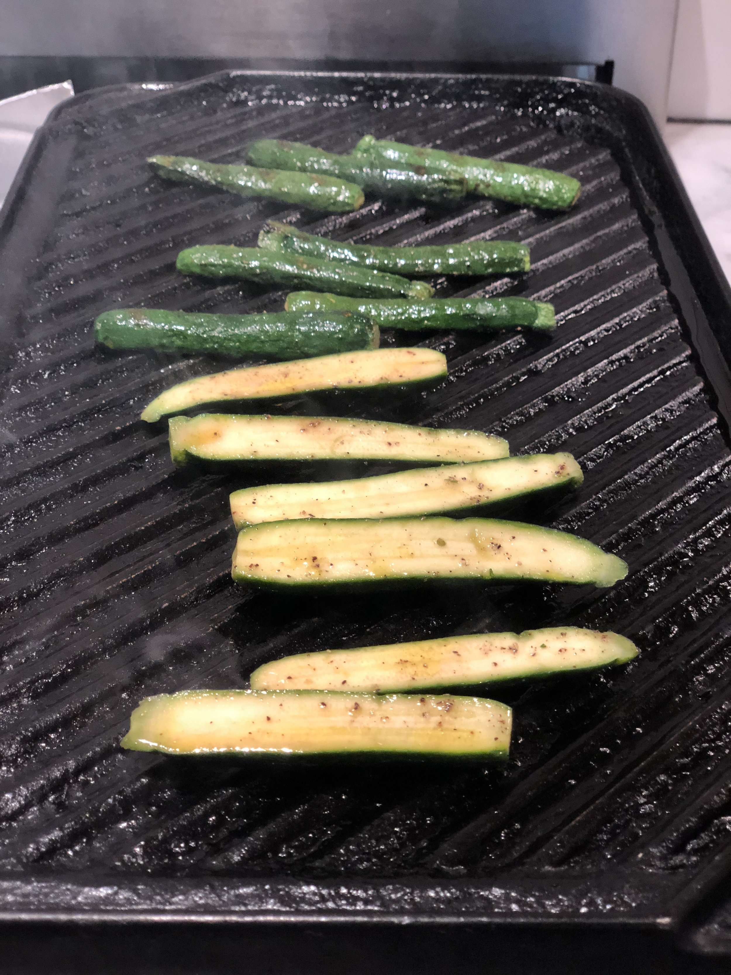 Cut the zucchini in half lengthwise and toss with olive oil and seasoning, place on a hot grill and cook until soft