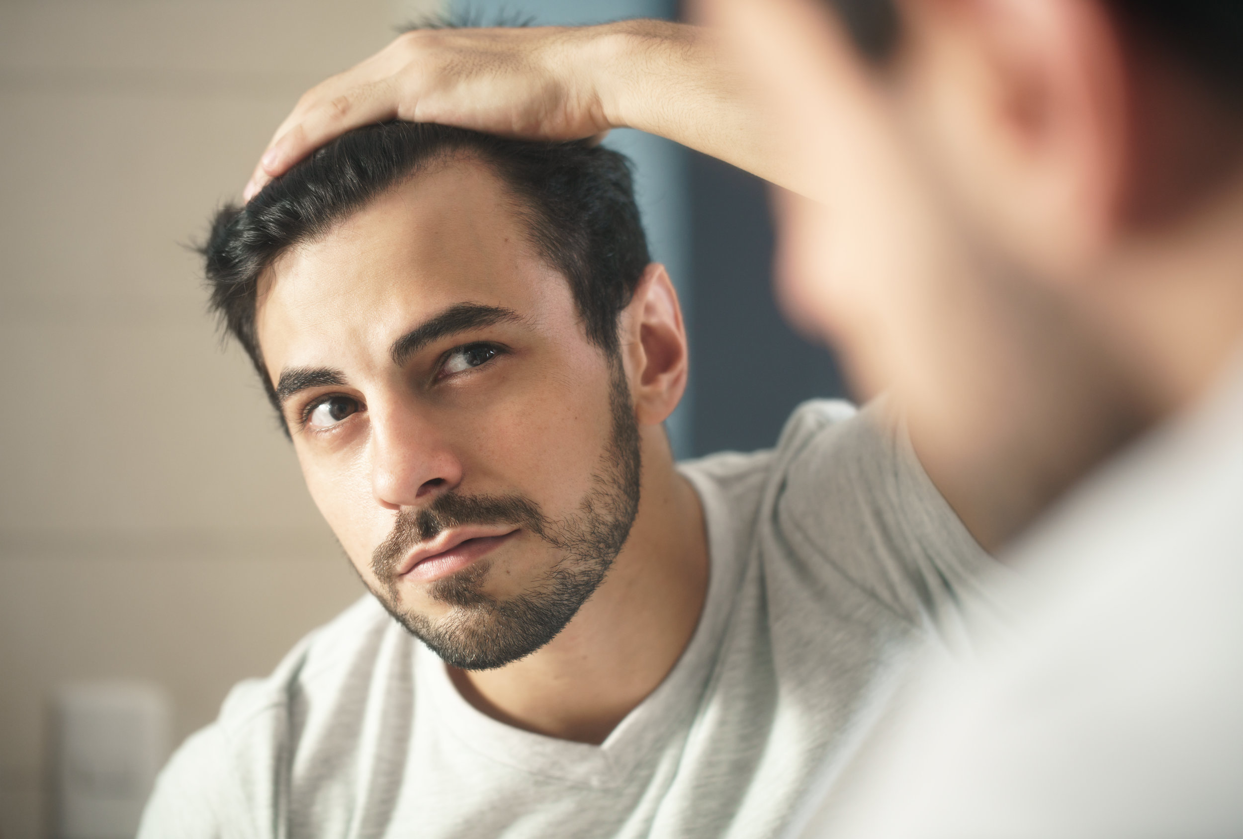man-worried-for-alopecia-checking-hair-for-loss-324FTZN.jpg