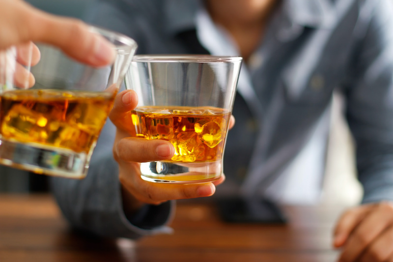 stock-photo-close-up-of-two-men-clink-glasses-of-whiskey-drink-alcoholic-beverage-together-while-at-bar-counter-730001233.jpg