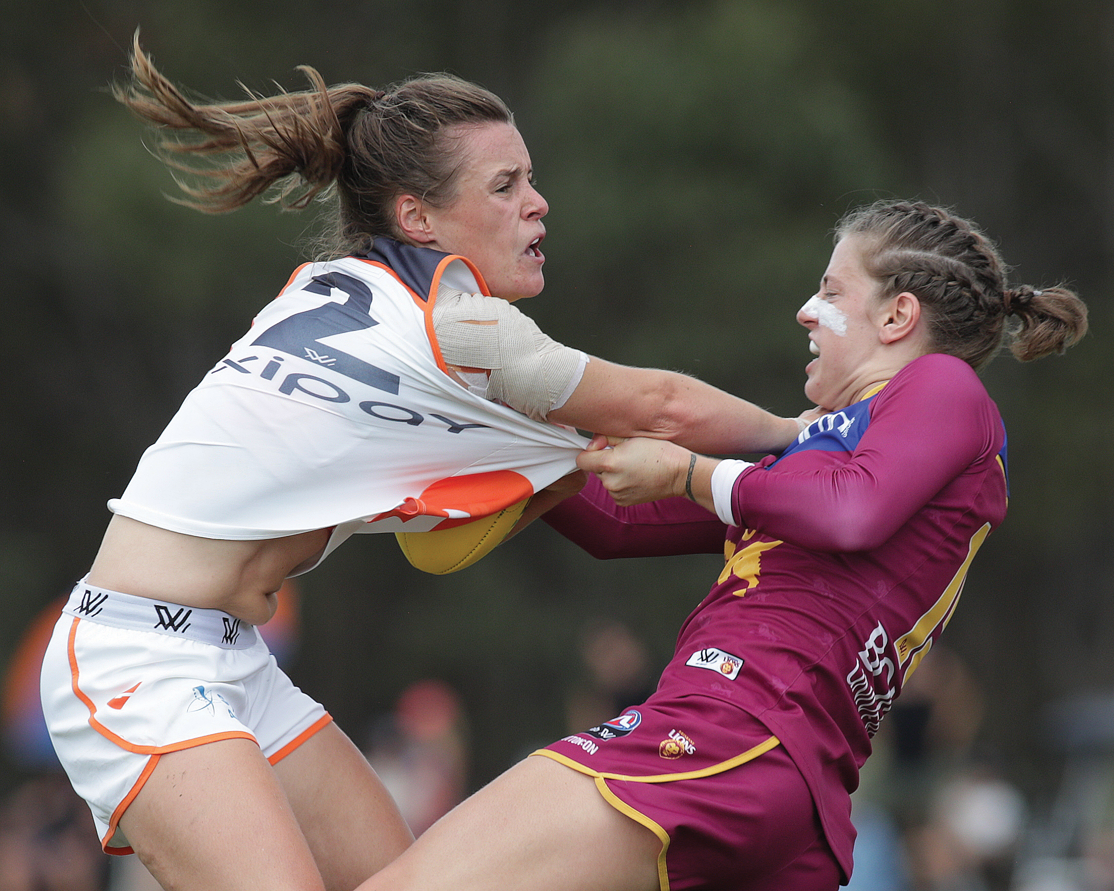 David Layden  'Don't Argue'  Alicia Eva fends off a tackle from Lions Nat Exon, QLD AFLW
