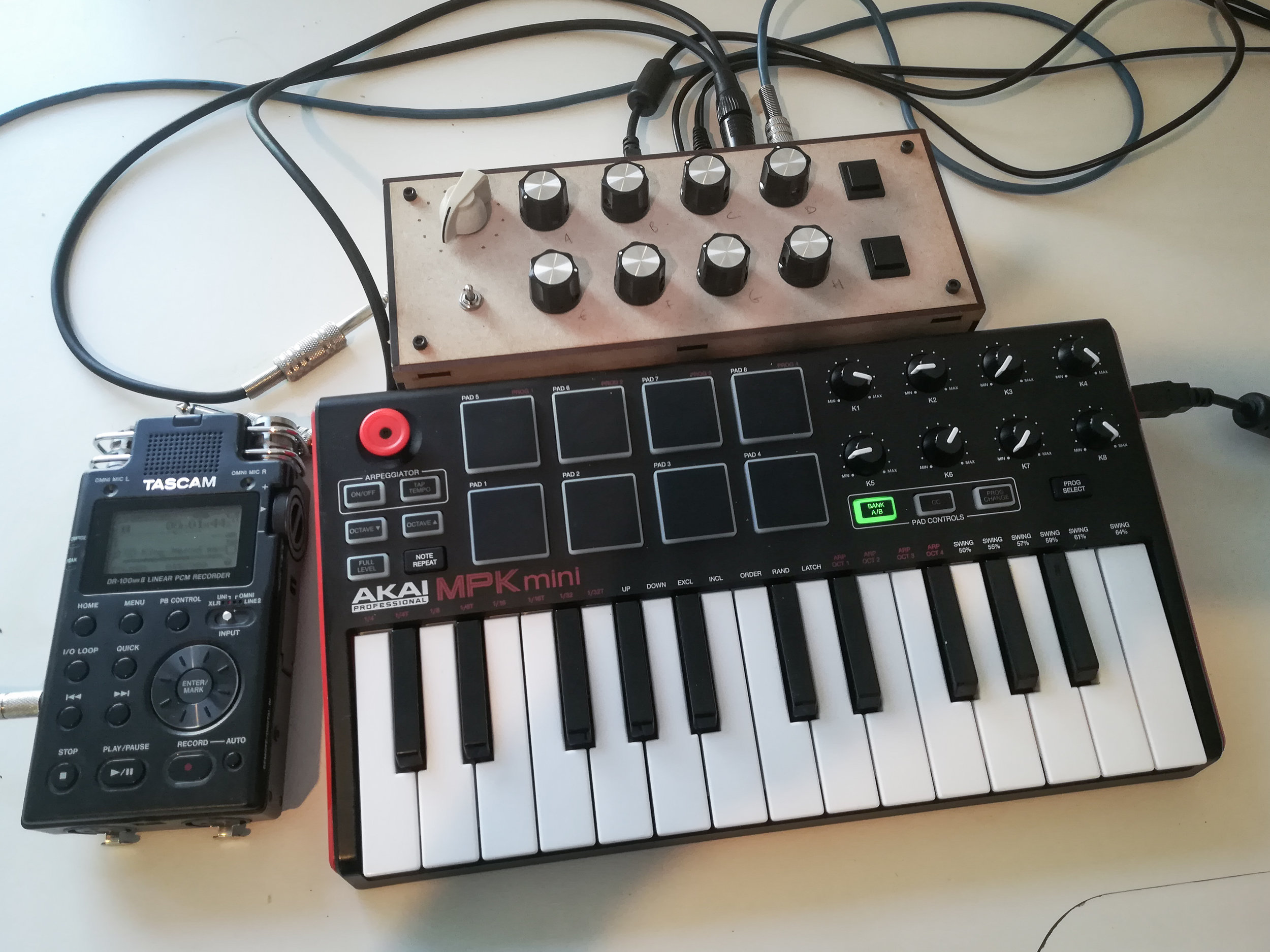 A simple set-up for live shows. - The interface interface for my Axoloti live set-up is very simple, just 8 pots 2 momentary switches, a toggle and a 12 position rotating switch.I mostly use the on board 12 bit ADCs to get about 30 times greater control resolution than regular MIDI CCs!!! This is awesome for precision movements, progressive and long evolution. More control and visual feedback can be achieved using SPI or I2C serial protocols. I am currently experimenting with rotary encoders to get rid of the rotary.I drew the case in Illustrator and used 3mm MDF and a laser cutter. The box design has jack inputs for expression pedals.I wired the MPK mini in MIDI for mapping notes and CCs and use Pgrm change for switching through patches. The Axoloti is polymorphic and is used for multiple sonic applications.