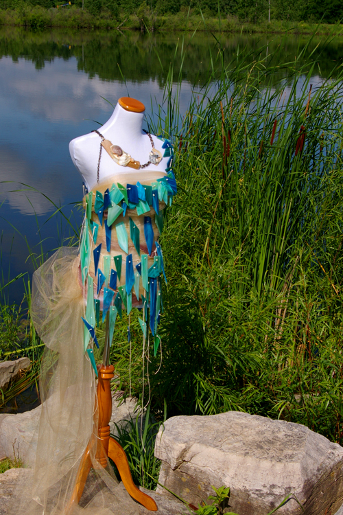 """As a Michigan native, Samantha was inspired to create a sculpture which would shed light on the fragile condition of our lakes and rivers.  Fractured Fashion  was the first of her dress collection and illustrated the movement of water via stained glass. Each shard of glass was hand cut to evoke broken droplets of water, which were then knotted together on a cotton corded """"net"""" laid to reflect the movement of water currents. The tulle base cascades off the right hip alluding to the flow of sand dunes. These coastal themes were accented with a necklace of found driftwood, shells, and distressed chain.   Fractured Fashion  was constructed in 2014 and originally installed in a restored furniture warehouse along the Grand River."""