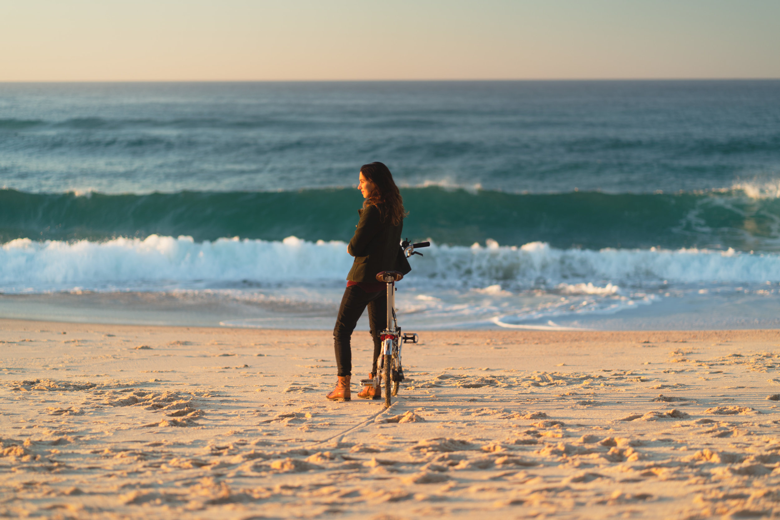 Girl watching the sunset at the beach with Brompton bike.