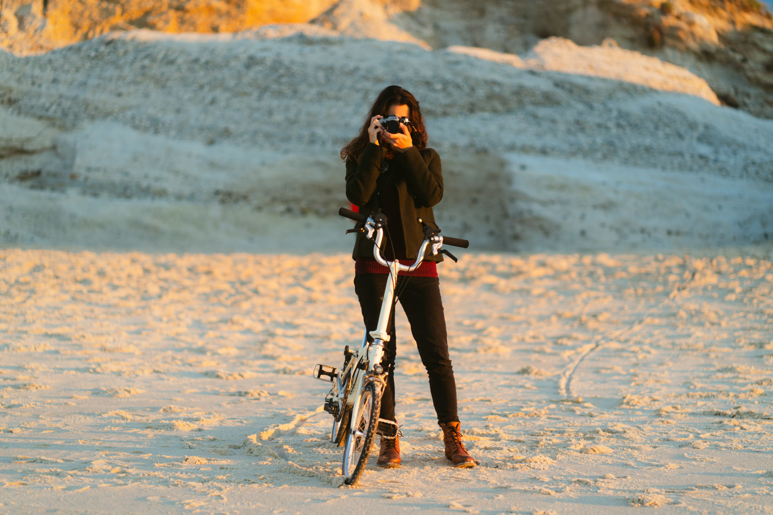 Girl with Brompton bike taking photos with vintage camera at sunset.