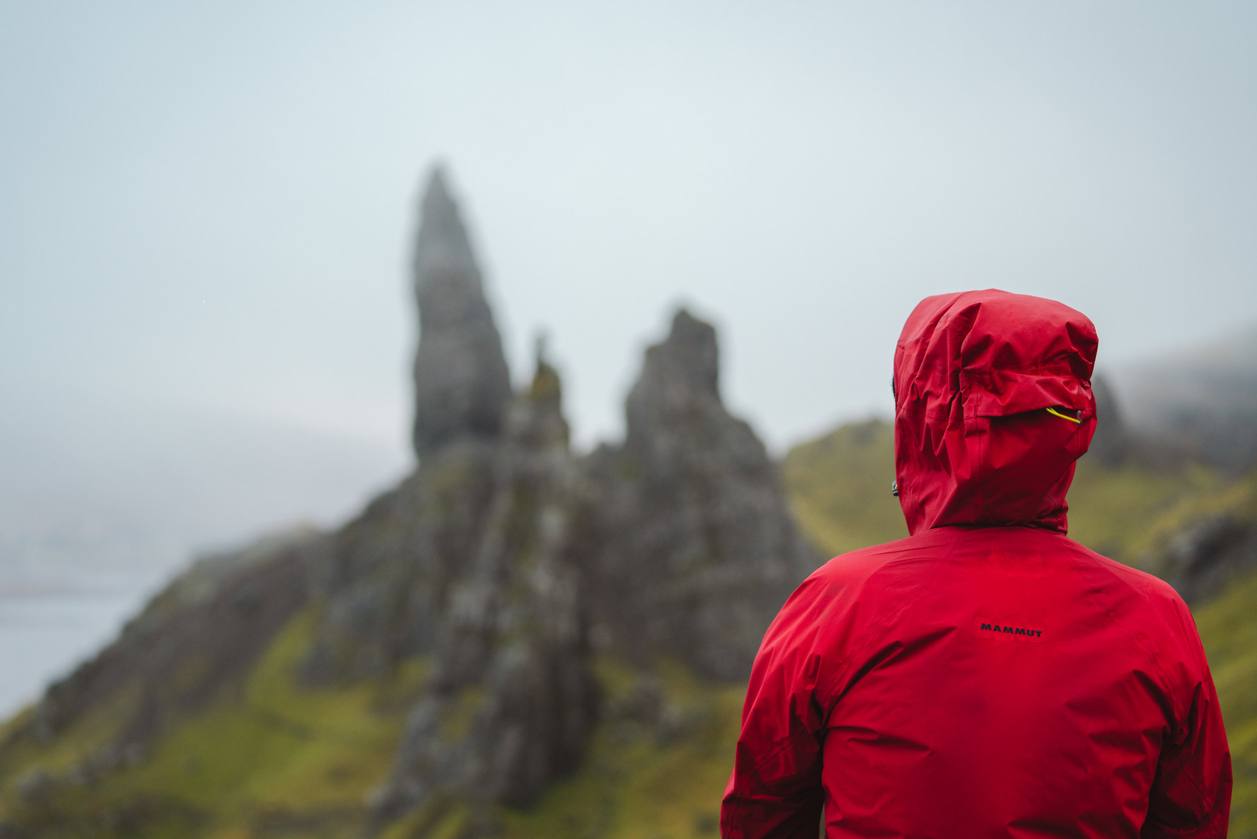 Man looking to Old Man of Storr with a Mammut red jacket