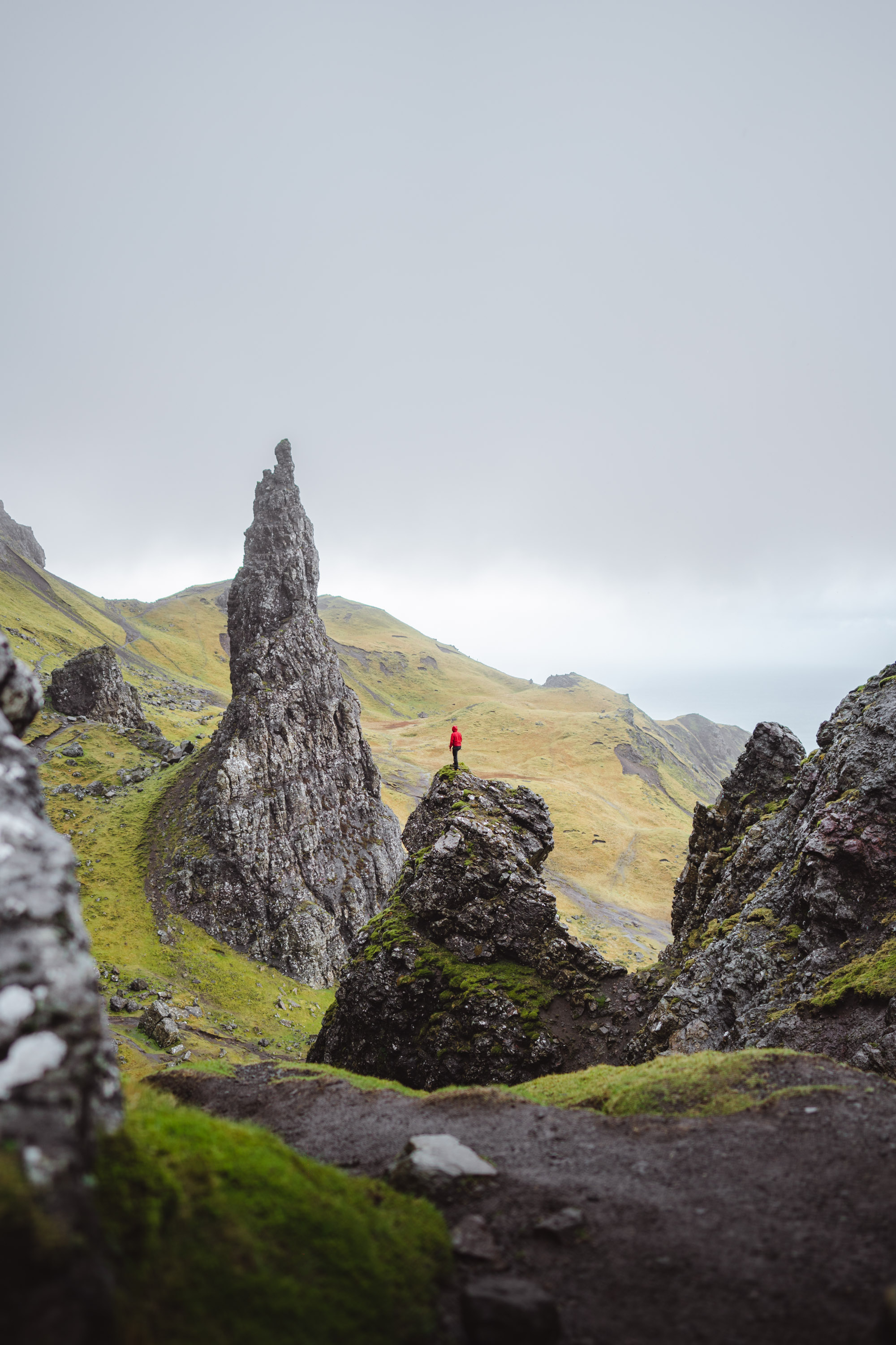Man with a Mammut red jacket climbing in Old Man of Storr, Scotland