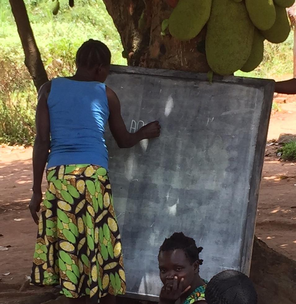 Anek writing her name on a chalkboard.
