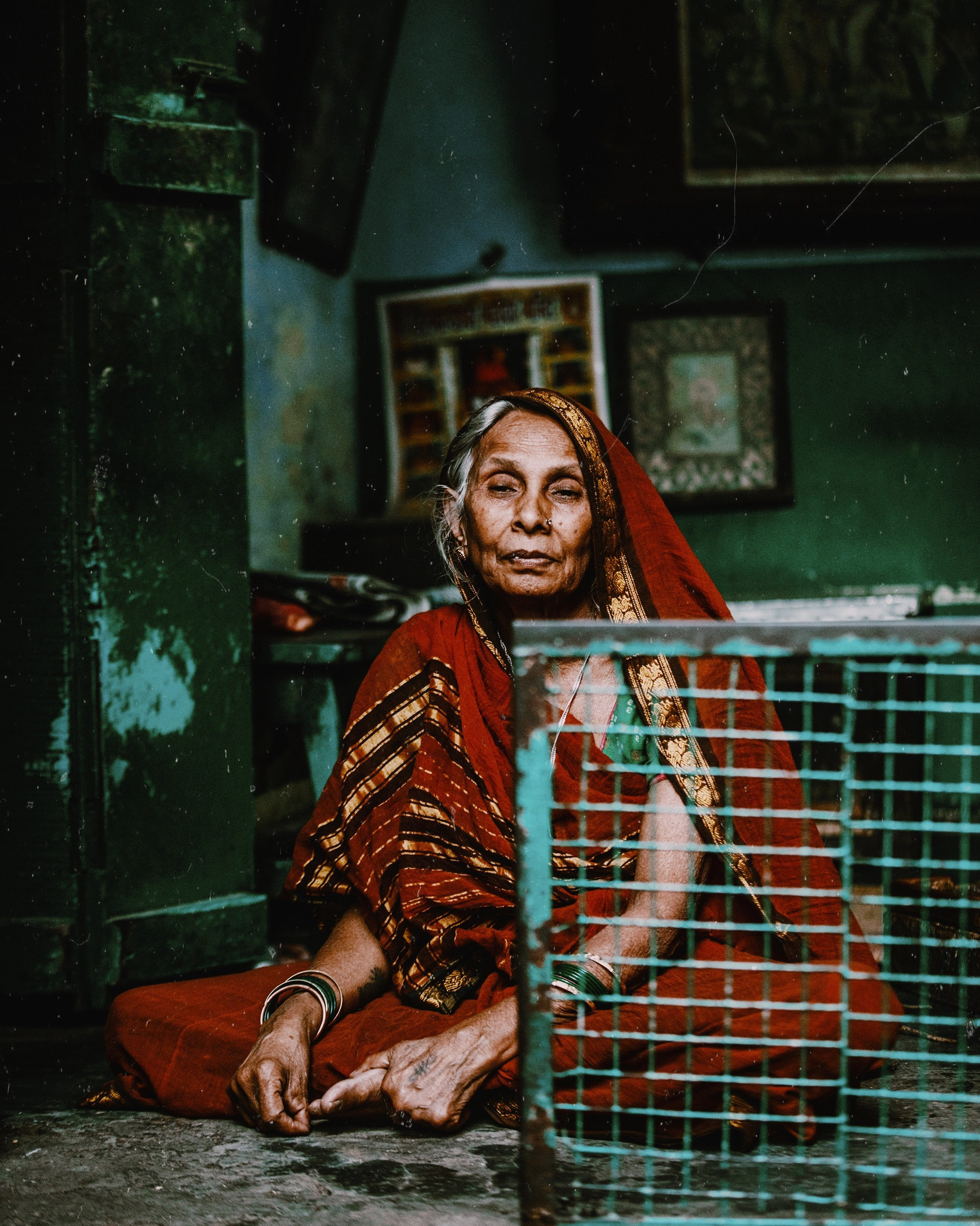 - A woman sits in a beaten down shop in the alleyways of Varanasi, India.