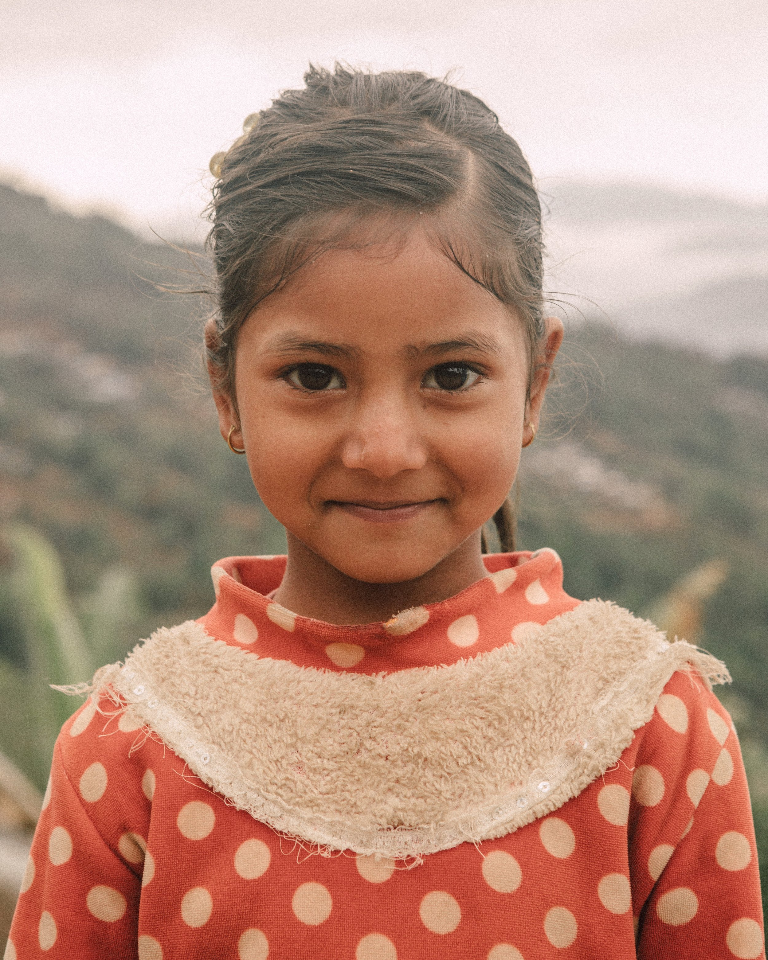 - A young Nepali girl takes a break from running down a mountain in a rural village to pose for my camera.