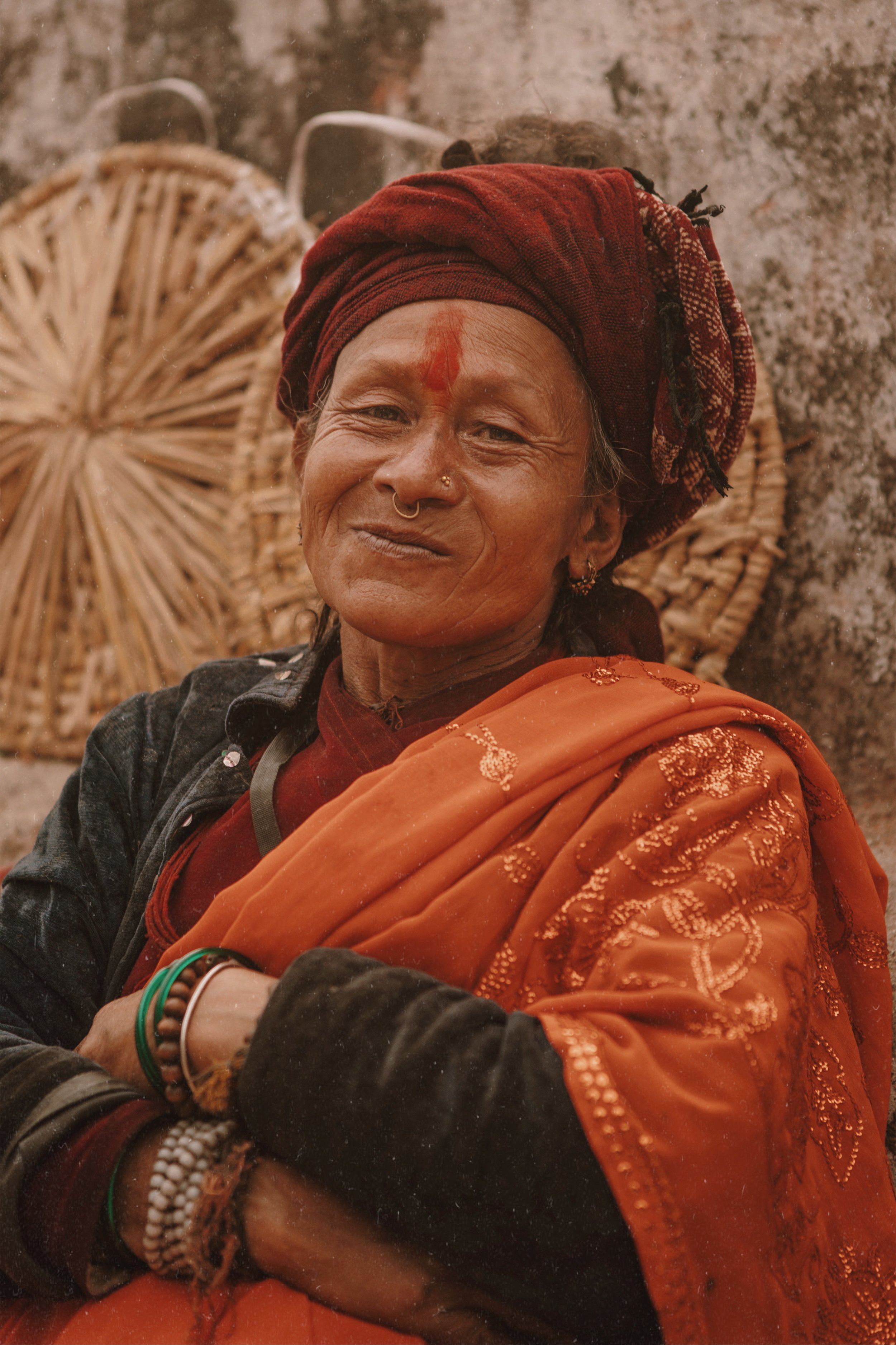 - A woman in Darjeeling, India selling baskets that she made by hand, takes a pause from her hustle to flash me a smirk.