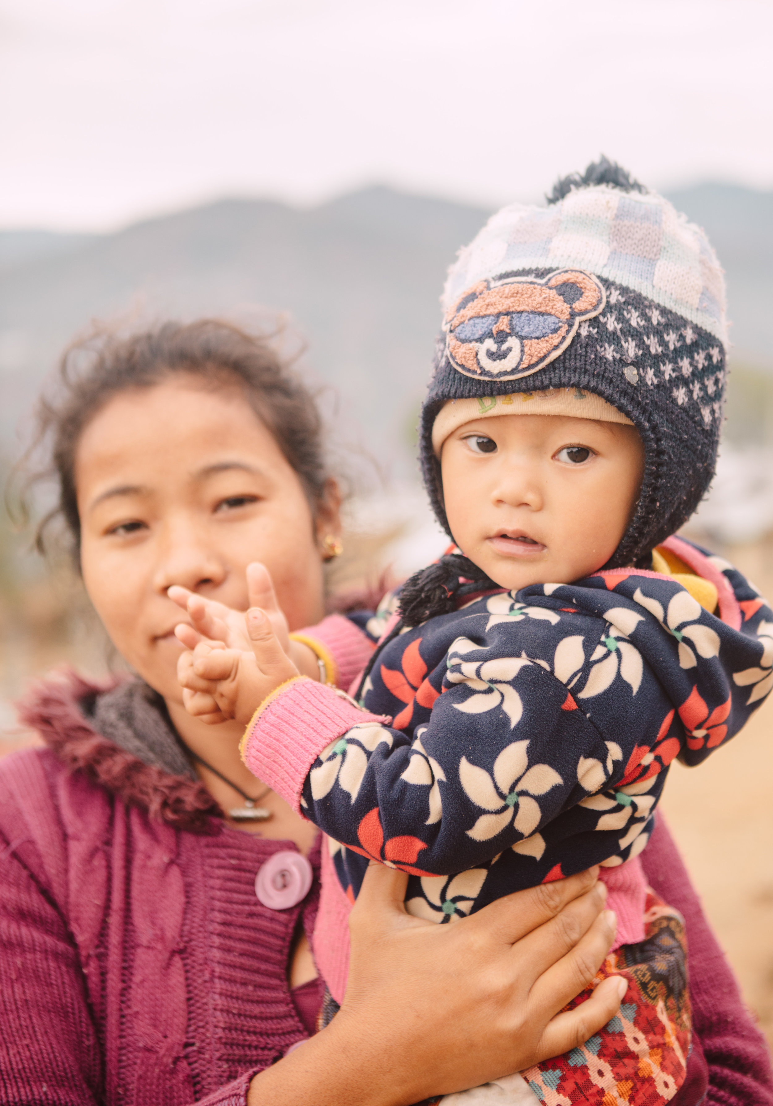 - A woman carries her child along the open mountain paths of Takure, Nepal. The child is intrigued by my camera, and I ask to take portrait.