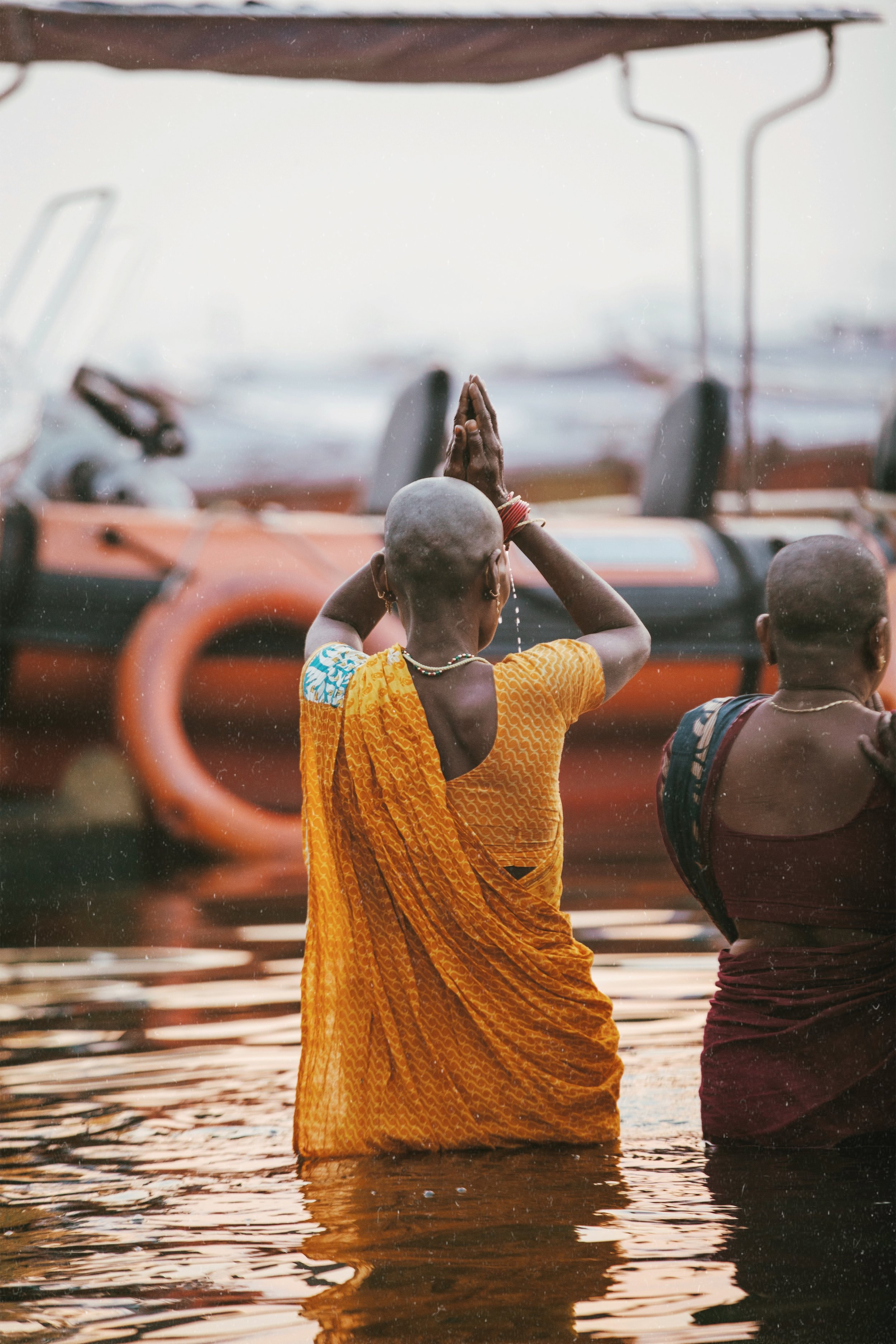 - Another woman with a newly shaved head offers up her morning prayers in the Ganges River — a morning ritual for the locals of Varanasi, India's holiest city.