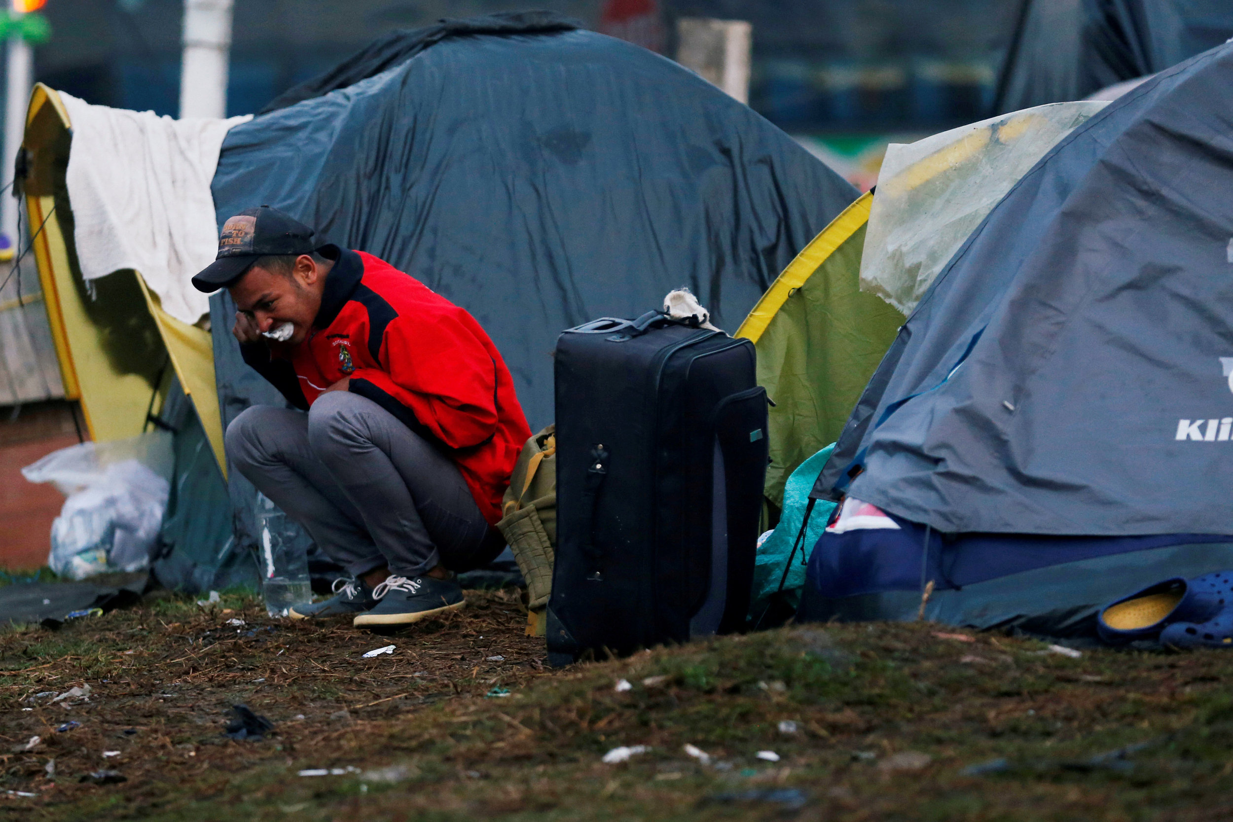 A Venezuelan migrant brushes his teeth outside his tent at a makeshift camp Nov. 26 in Bogota, Colombia. [Photo: NS photo/Luisa Gonzalez, Reuters]