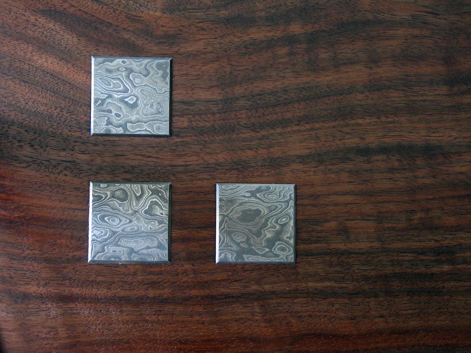 Inlaid Damascus steel medallions on top surface