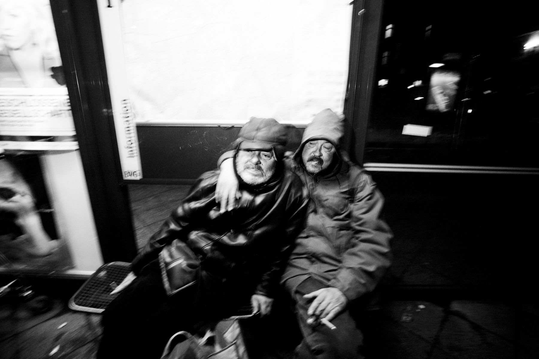 Two friends, homeless, drunk at the bus stop. Berlin 2013.
