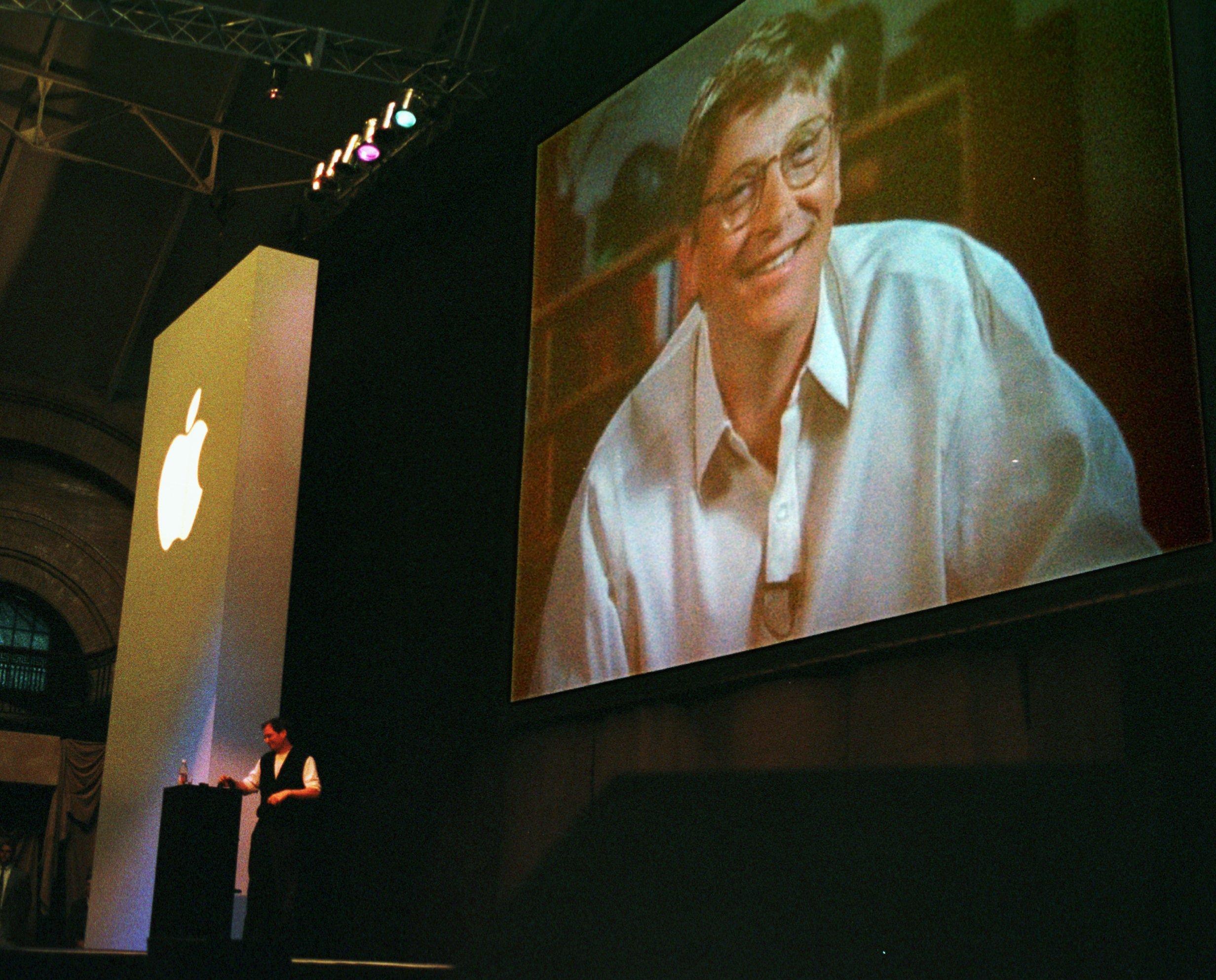 Bill Gates hovering over Jobs at MacWorld Boston 1997 .