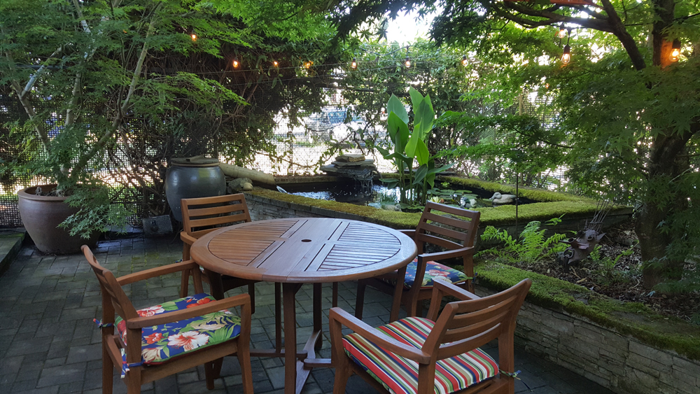 The living space extends outside to this patio that features large potted plants and a koi and goldfish pond.