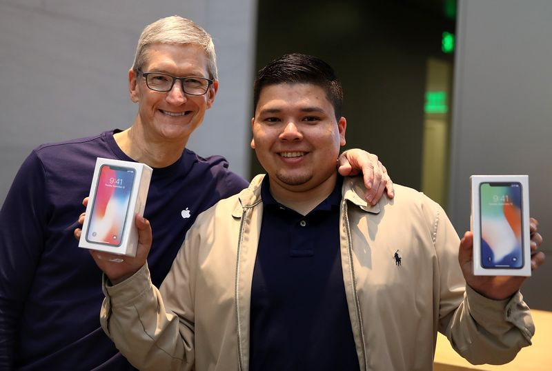 Apple CEO Tim Cook takes a picture with David Casarez, who purchased an iPhone X, at a store in Palo Alto, California on Nov. 3, 2017.  Photographer: Justin Sullivan/Getty Images