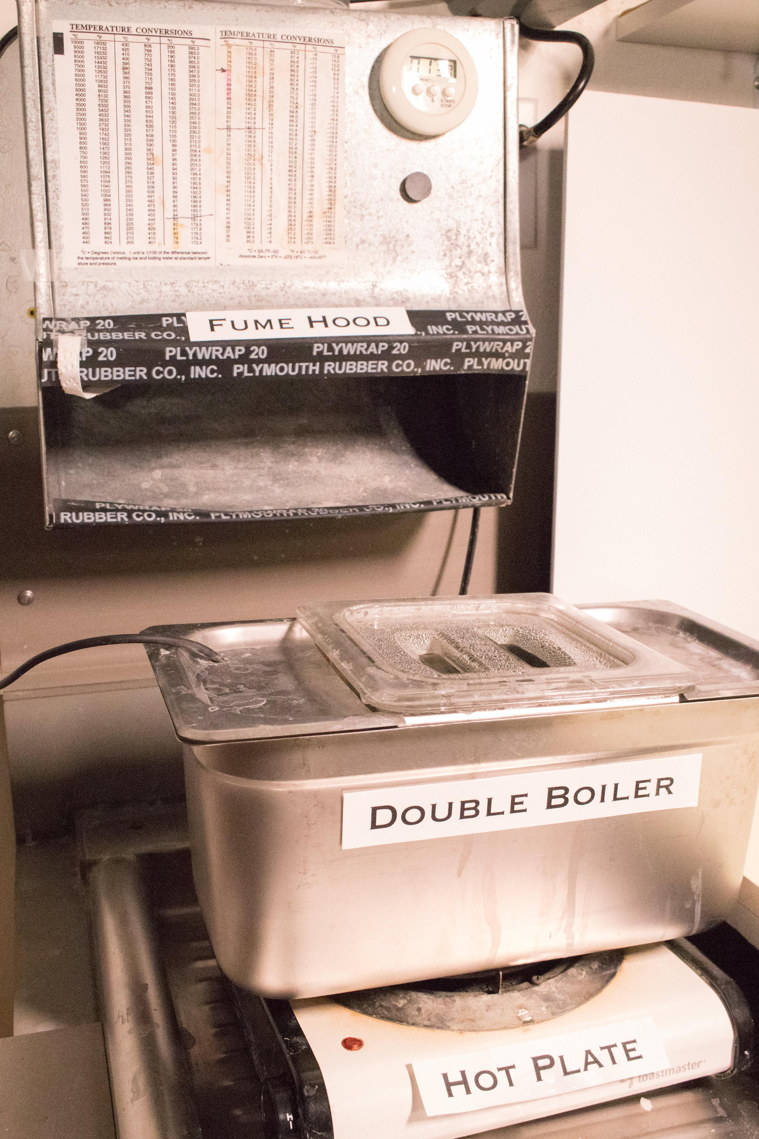Double boiler placed beneath a fume hood in laboratory.