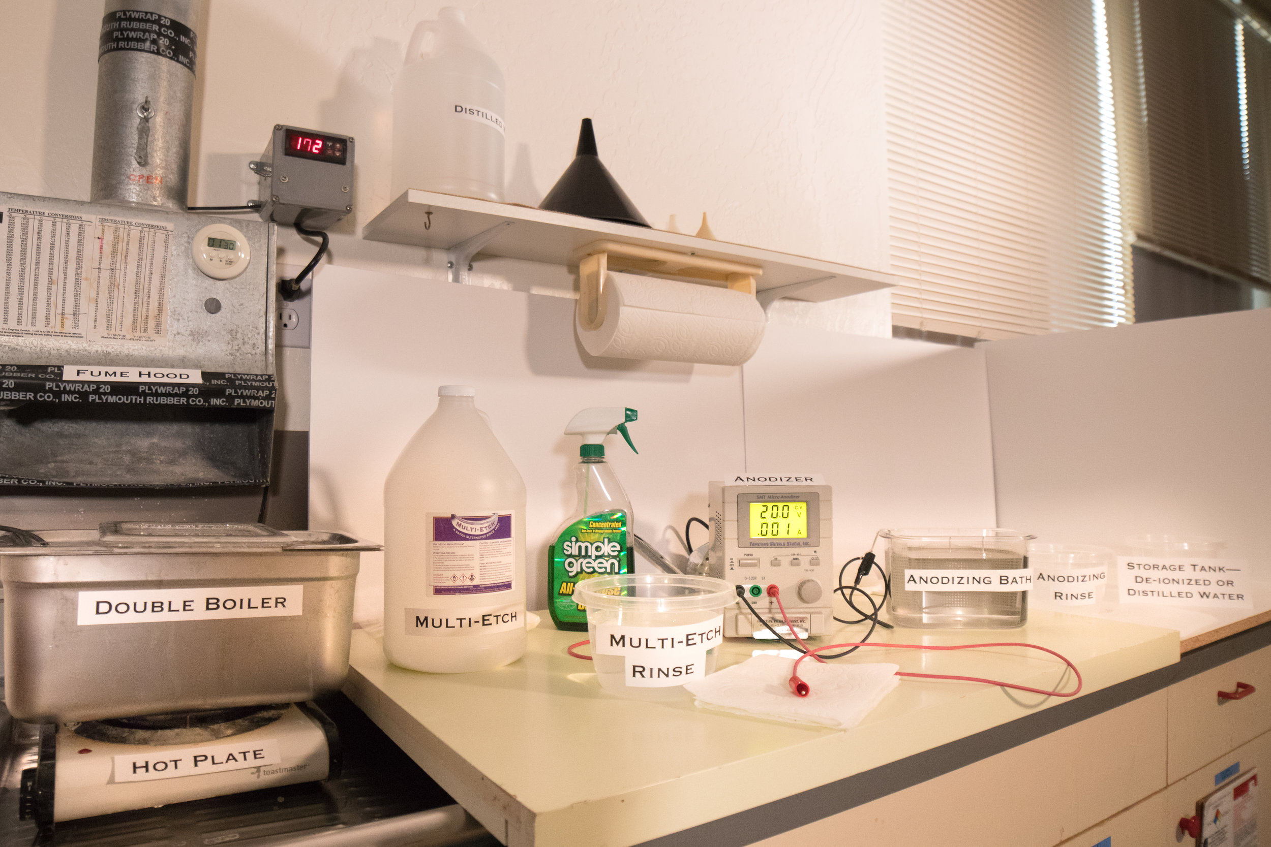 Potential anodizing lab set-up. Lab set-up features a double boiler beneath a fume hood, jug of Multi-Etch, a rinse bowl, cleaning solution, anodizing machine next to anodizing bath, bowl for anodizing rinse and a storage tank marked for de-ionized or distilled water.