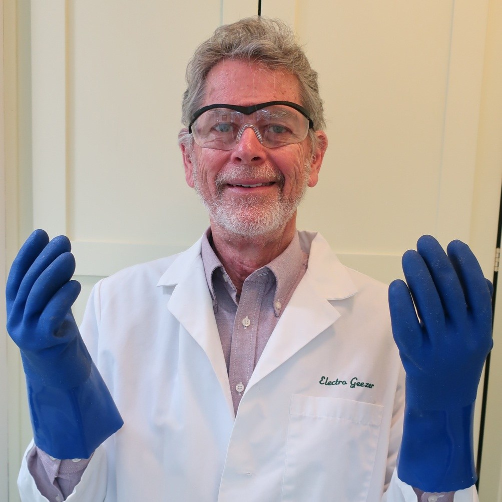 Chris Boothe wearing safety goggles, safety gloves, and a lab coat.