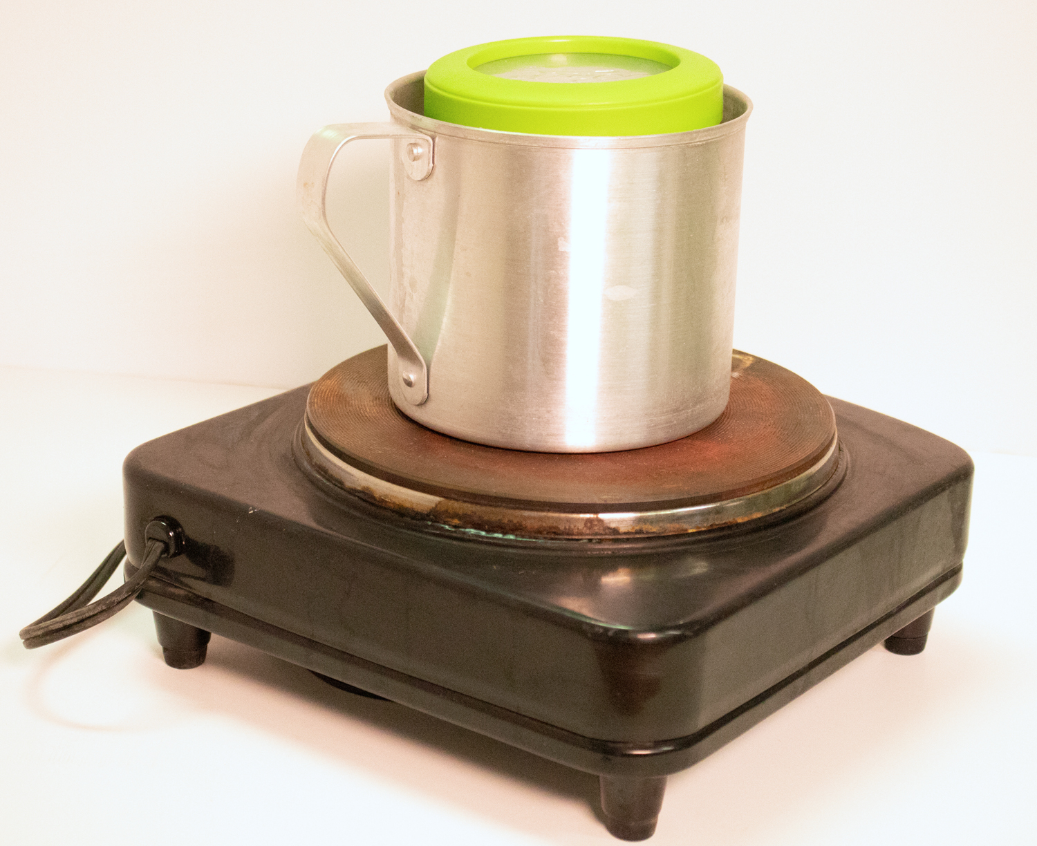 Side view of double boiler made with metal container, plastic container and hot plate.