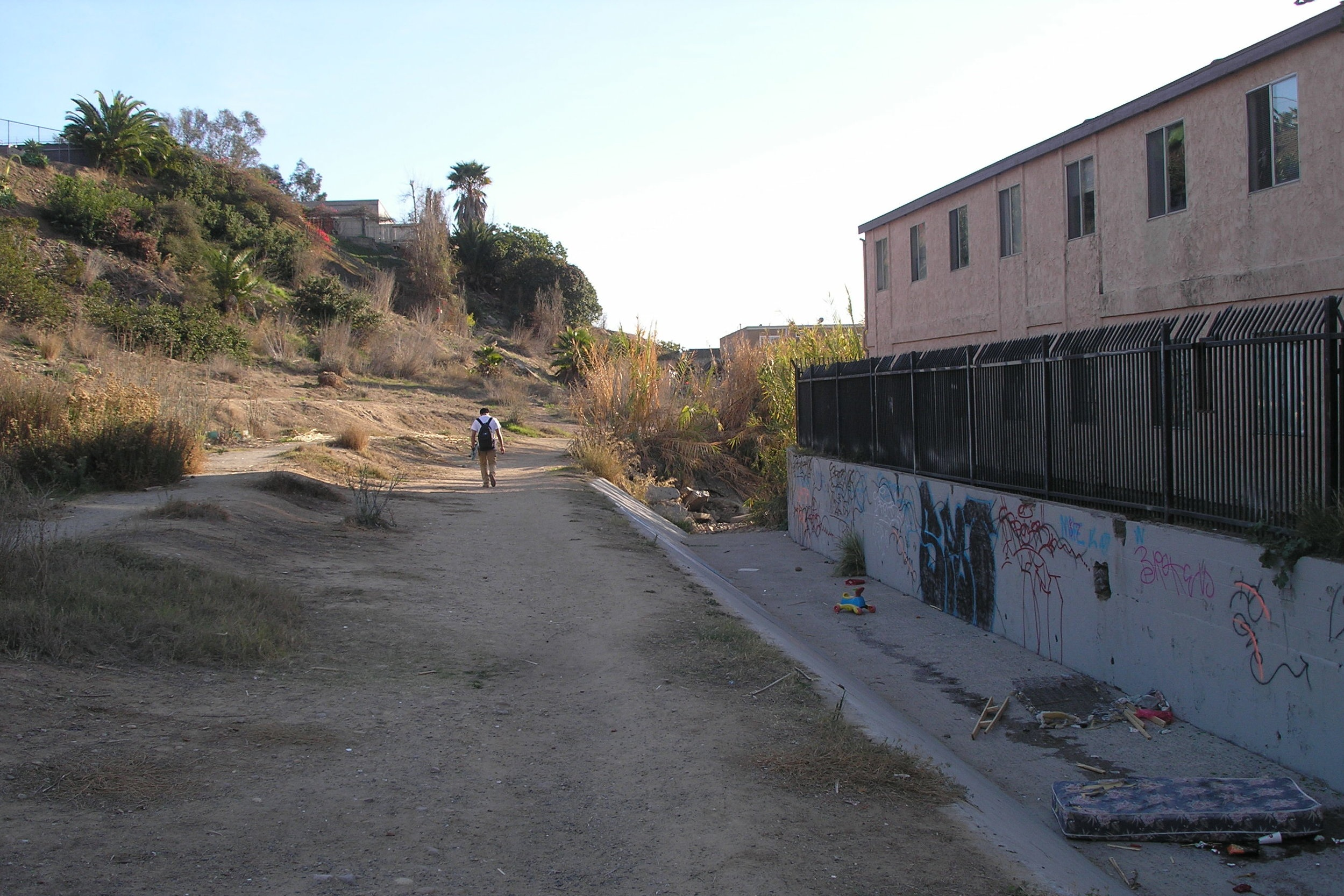 BEFORE:  Auburn Creek in City Heights in 2014 filled with trash and invasive species. This area experienced fires and criminal activity, making it unsafe for the adjacent Somali refugee community, Bandar Salaam,