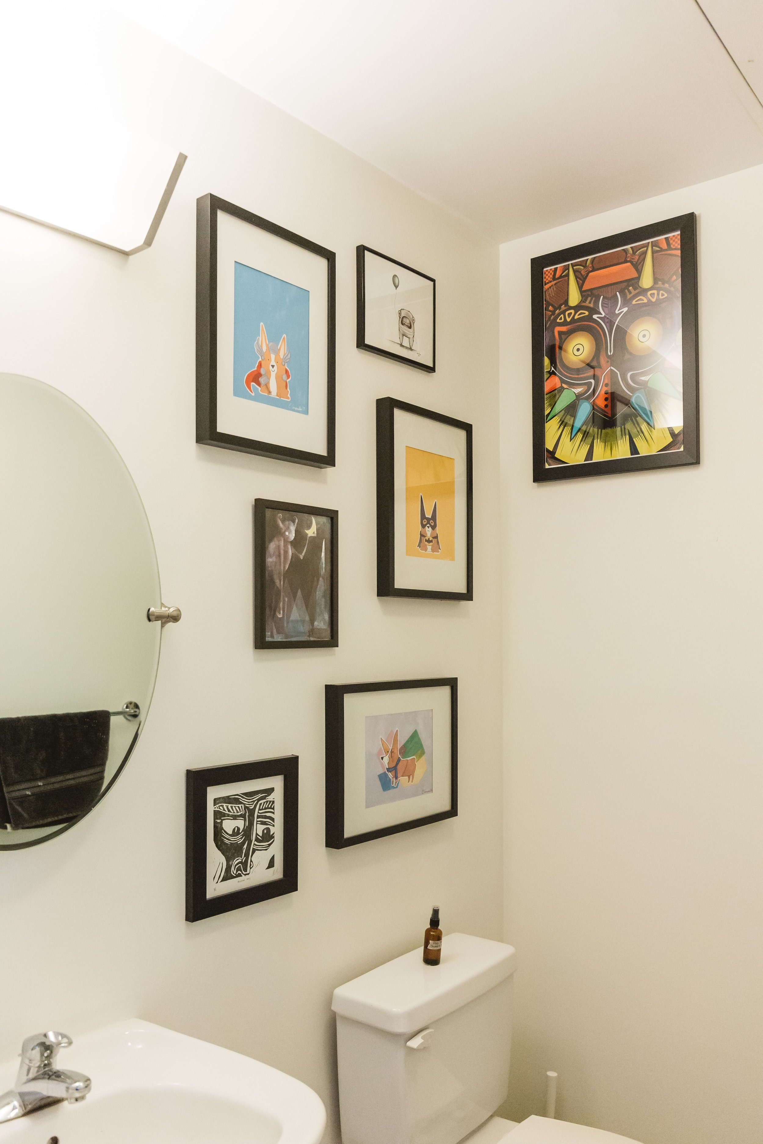 Black frames stand out against the white walls in the bathroom, and add a fun and colorful twist on bathroom decor.