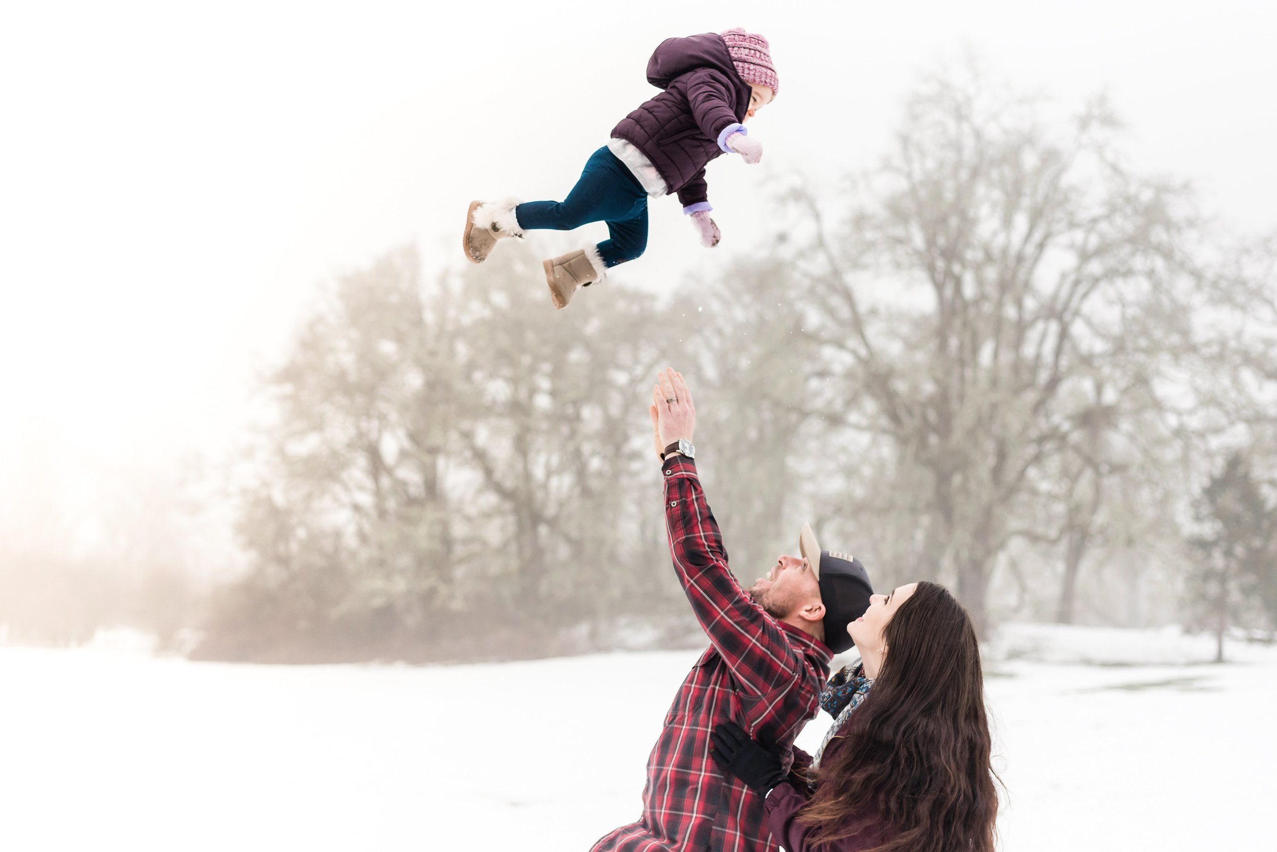 Father throwing daughter in the air for a photo