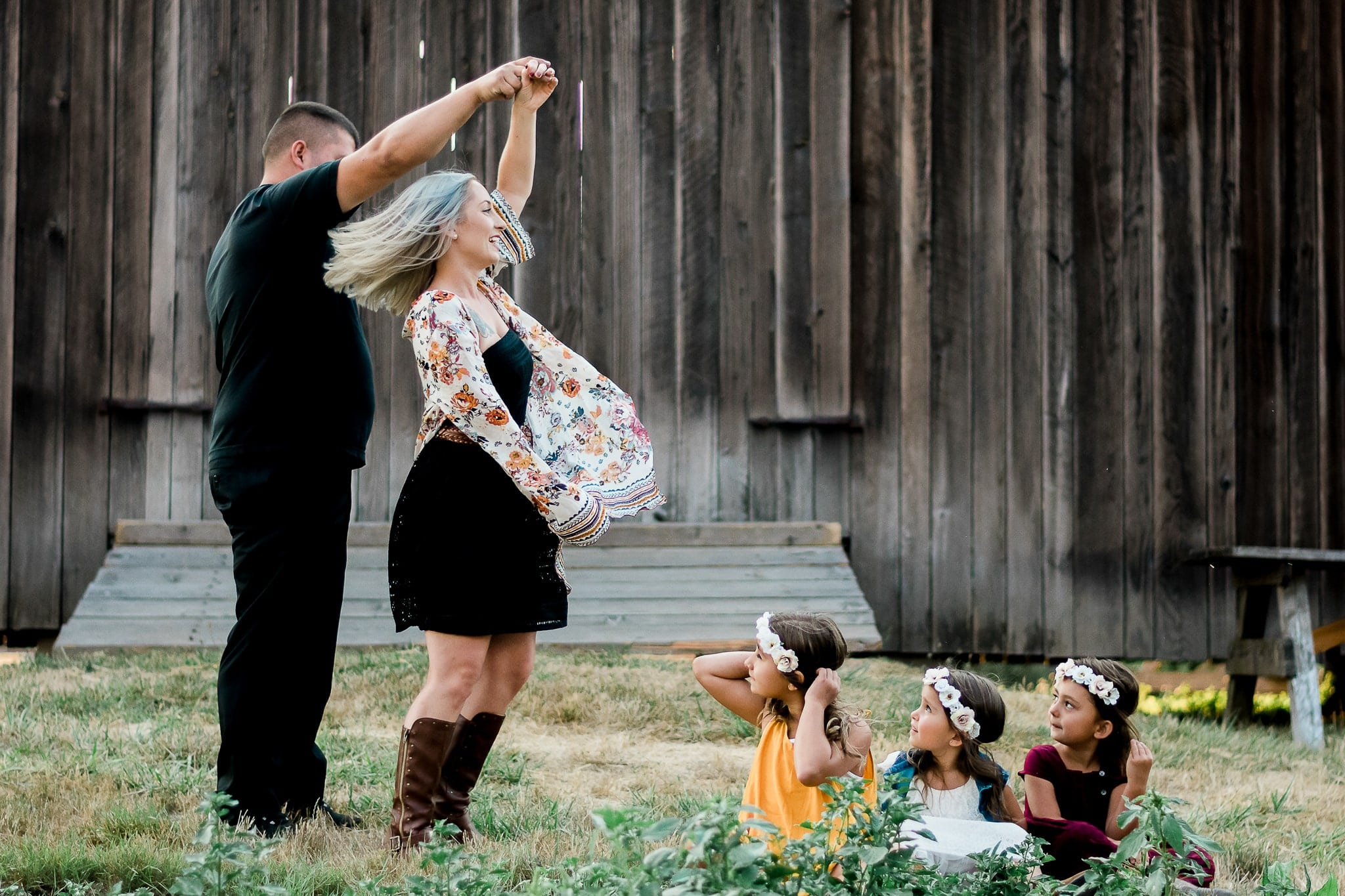 A family posing for a photoshoot by a rustic barn