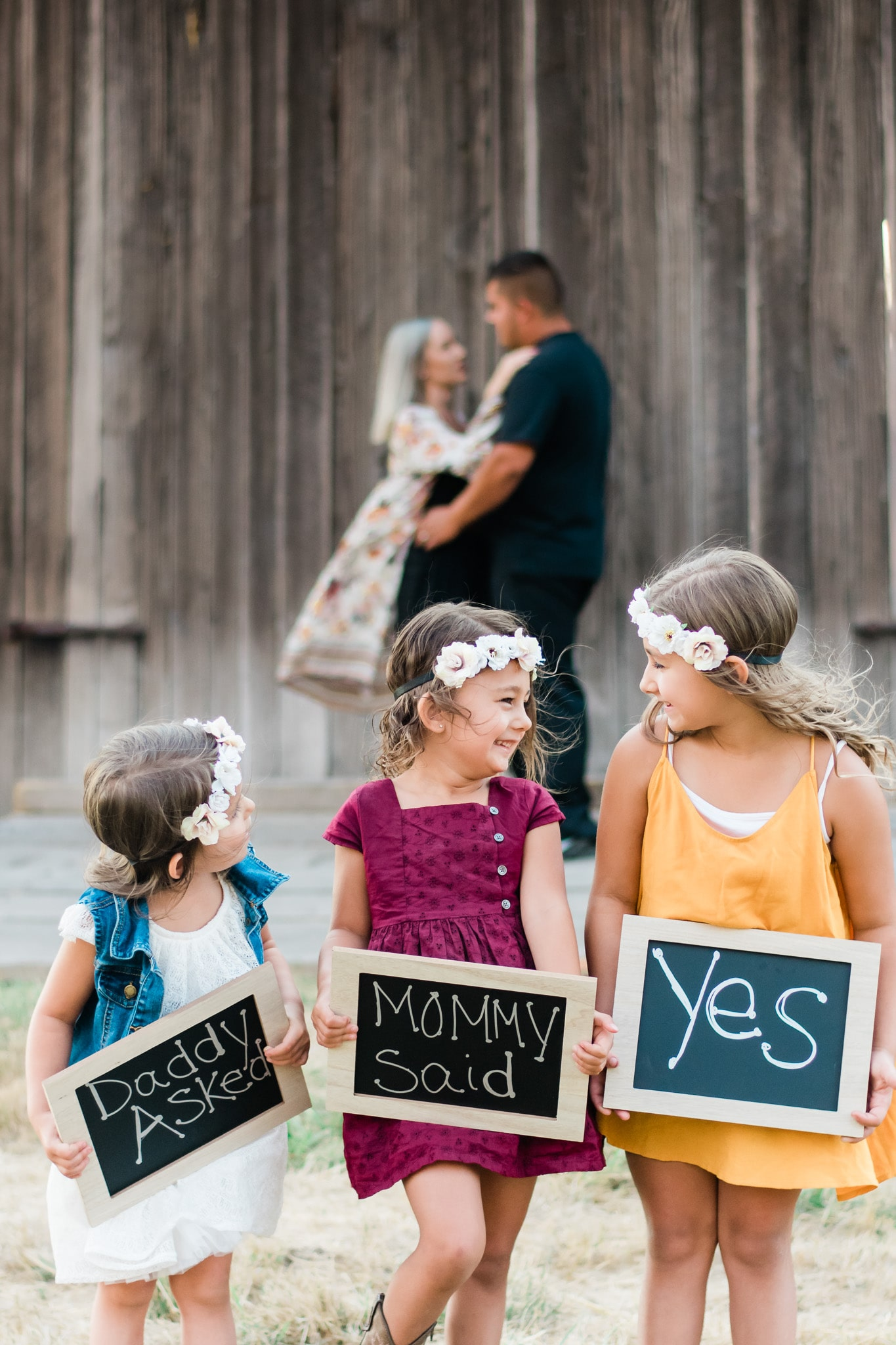kids holding a sign to celebrate their parent's engagement
