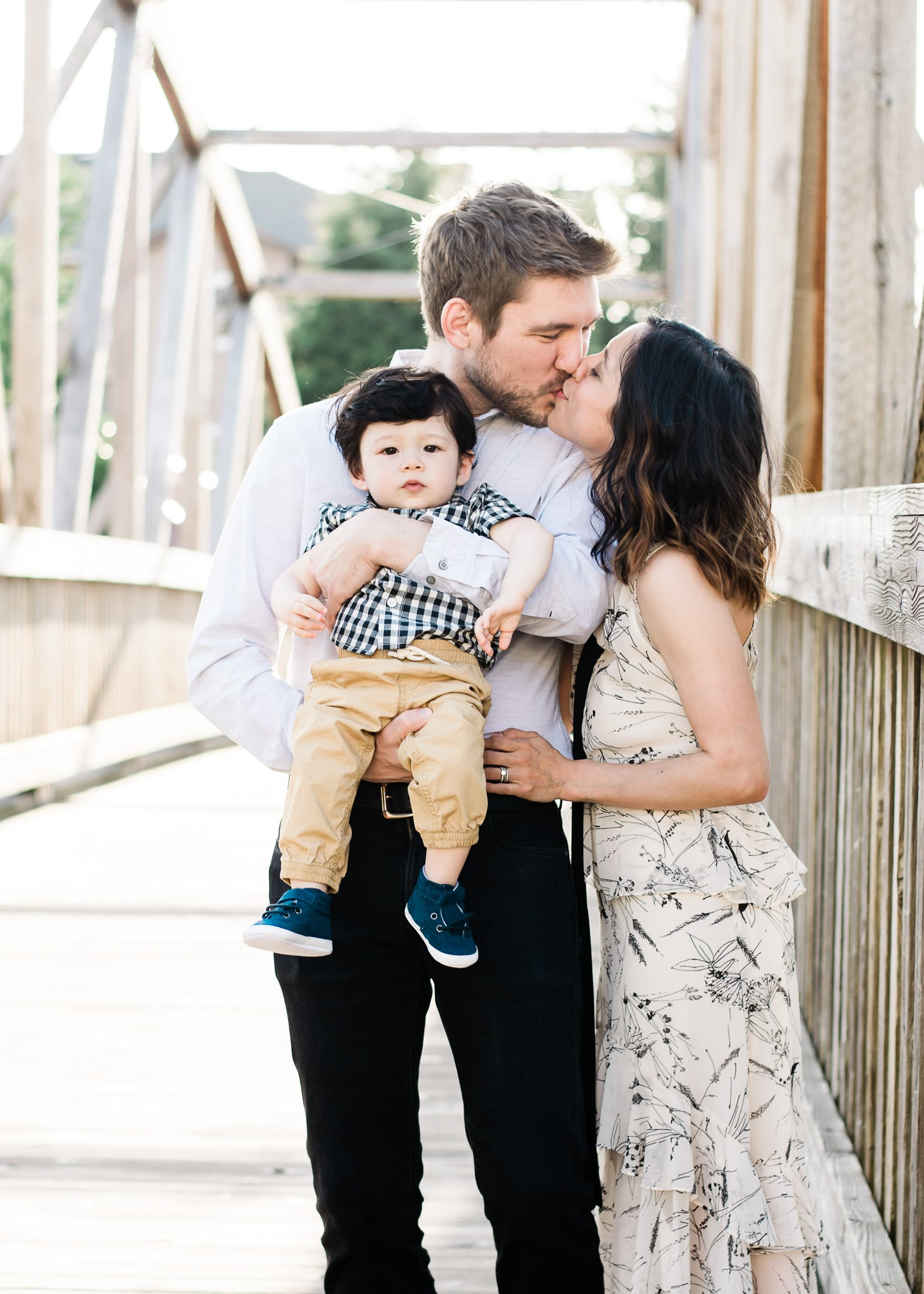 A one year old milestone photo with parents kissing.