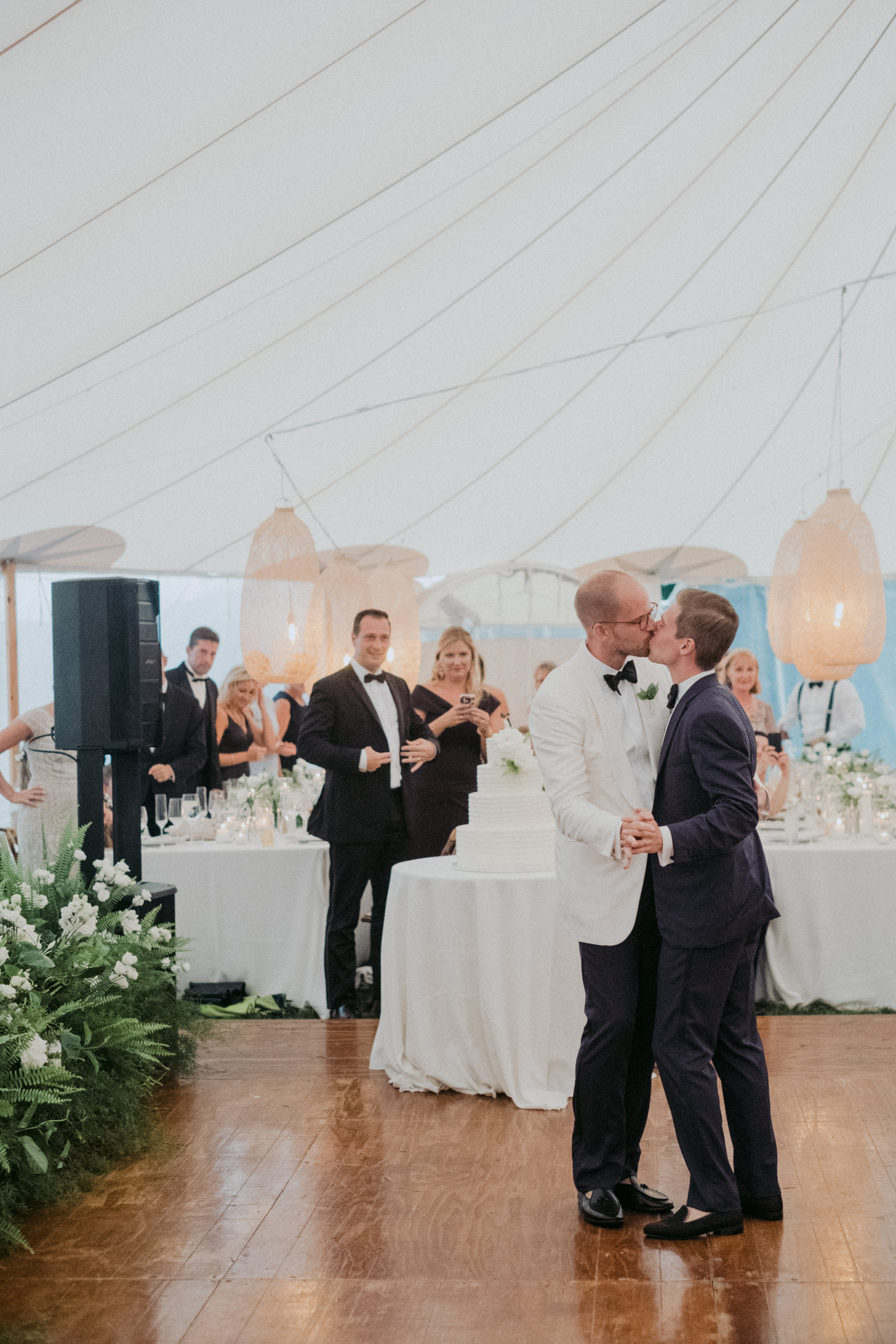 Same Sex Wedding in Provincetown, MA. Destination wedding planned by Nicole Simeral. Coastal Chic Wedding, Travel Wedding, Sperry Sailcloth Tent Wedding, bamboo folding chairs, Belfast linen, whites and greens , straw lantern, symmetry , first dance, wedding kiss