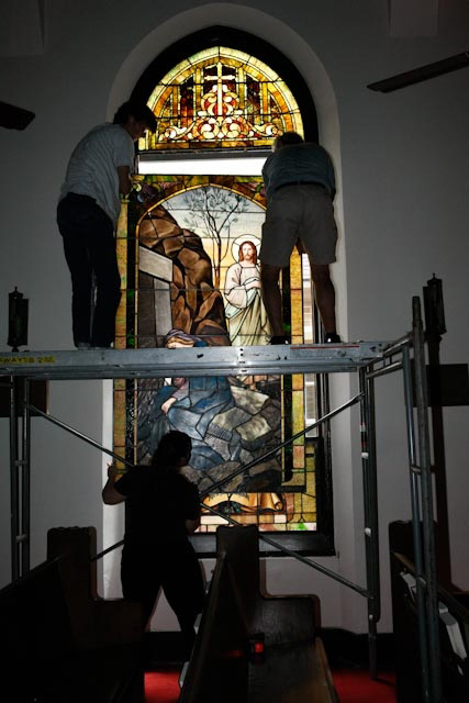 FINAL STEP  Rob, Michael, and Heather lift a restored window back into its frame.