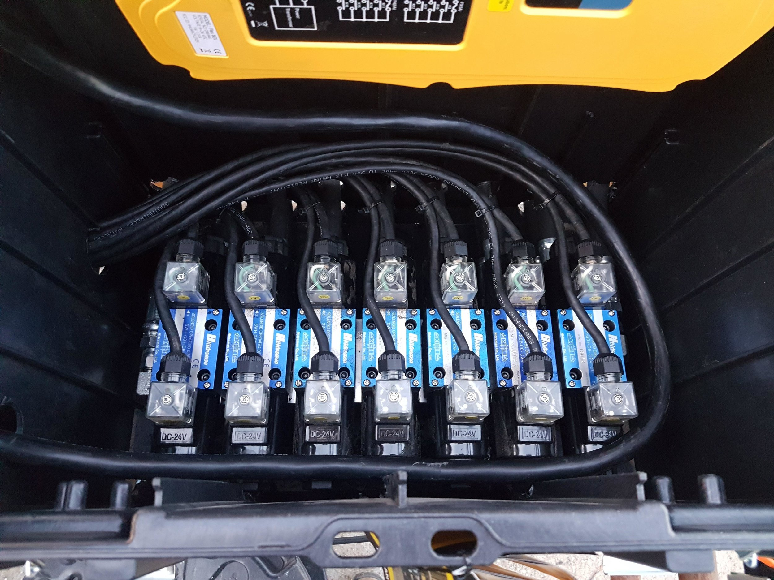 A bank of 7 valves mounted on a single manifold. The valves are inside a large toolbox to protect them from the weather.