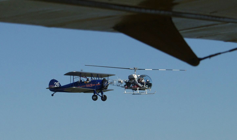 Bell 47 and biplane flying together