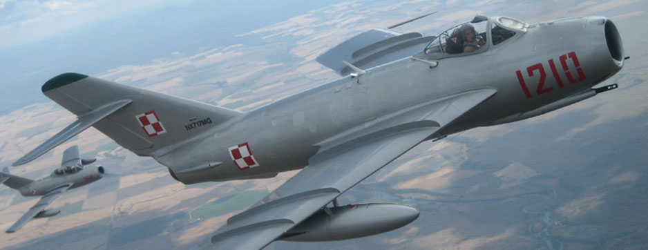 Mikoyan-Gurevich MiG-17 flying over field with MiG 15