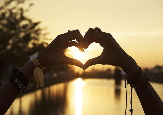 Heart hands watching sunset