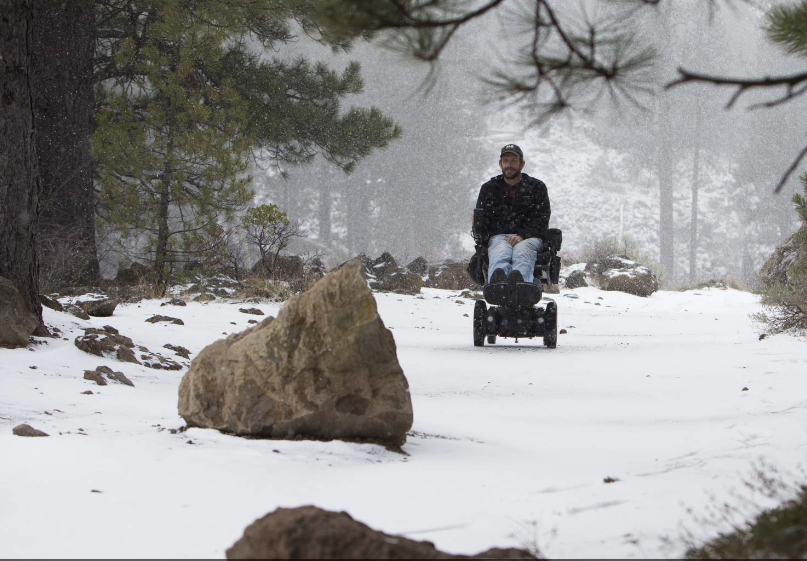 La Pine resident Jabe Couch, who has multiple sclerosis, enjoys an outing in his wheelchair near Benham Falls on Feb. 14, 2018. Couch is saving for an off-road, arm-powered wheelchair that will let him explore off-trail more easily than his electric wheeelchair, whose battery is quickly depleted by cold and heat. (Andy Tullis/Bulletin photo)