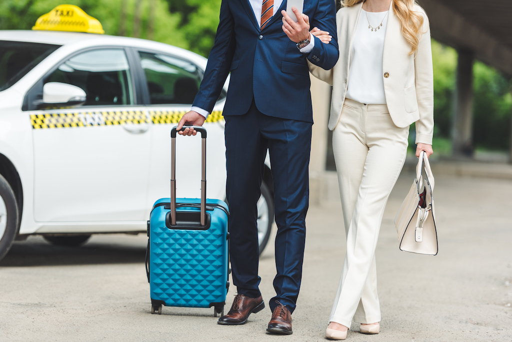 Cropped-shot-of-stylish-young-couple-with-suitcase-going together-near-taxi-cab.jpg
