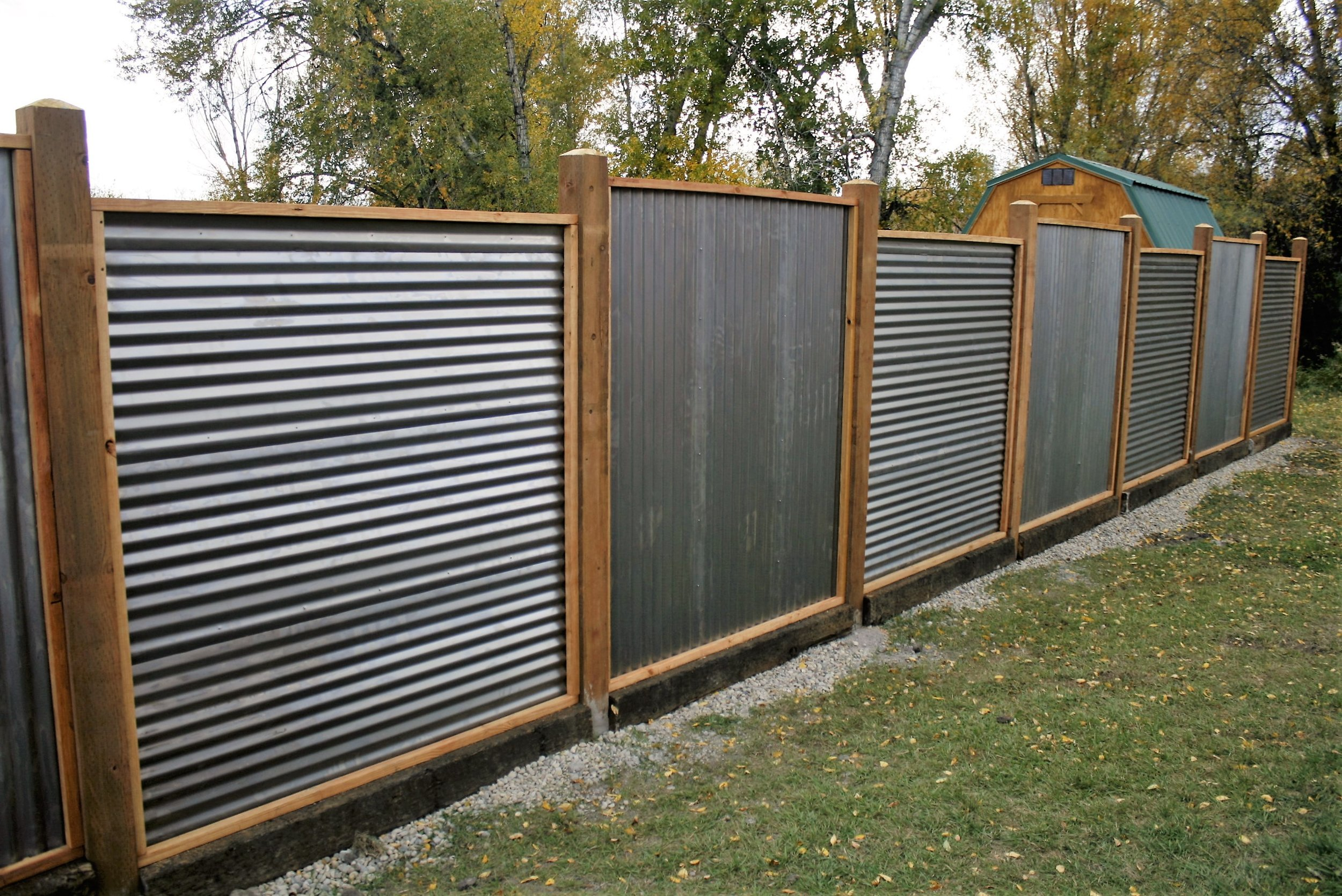 8 foot fence with railroad tie base, rusted metal sheeting, clients design
