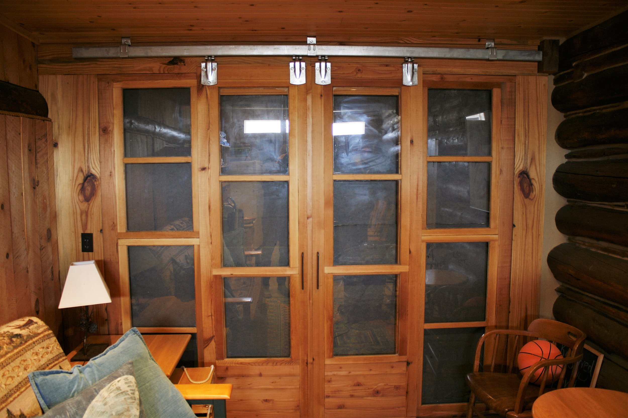 Sliding doors built using old storm windows found on the property