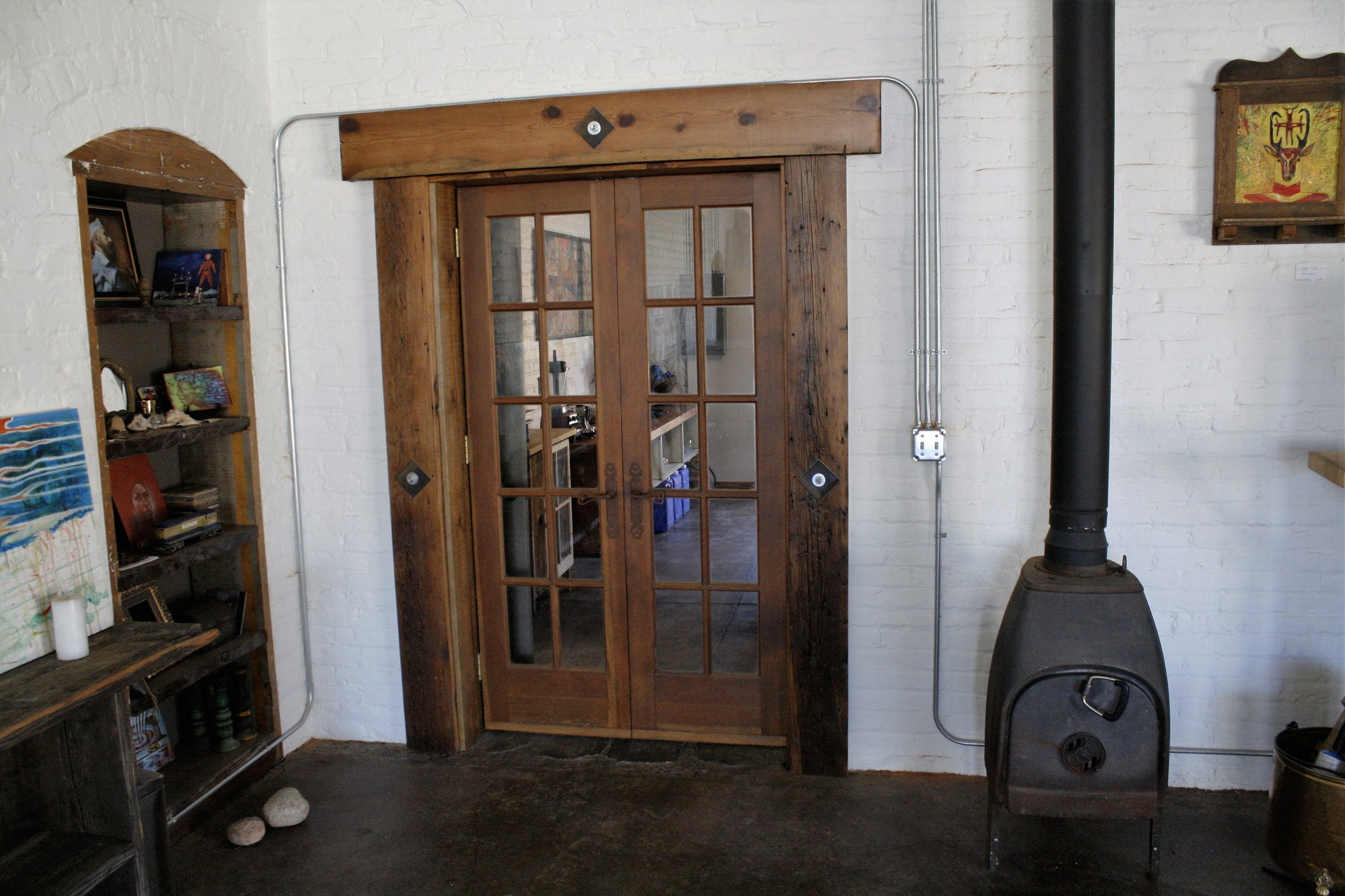 Custom made french doors, 2x8 reclaimed trim, wood stove install and inset bookshelf