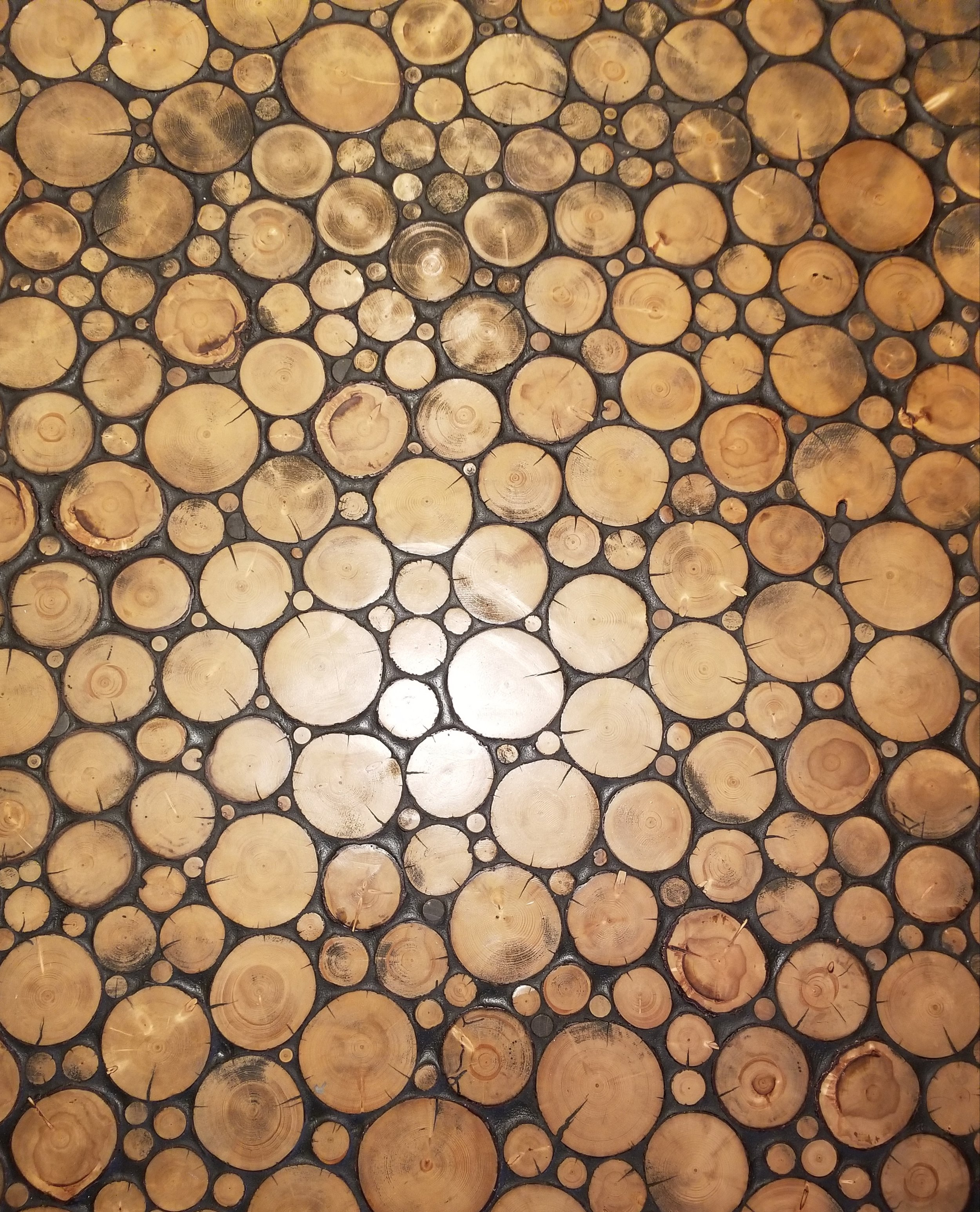Close up of wood rounds floor with black grout