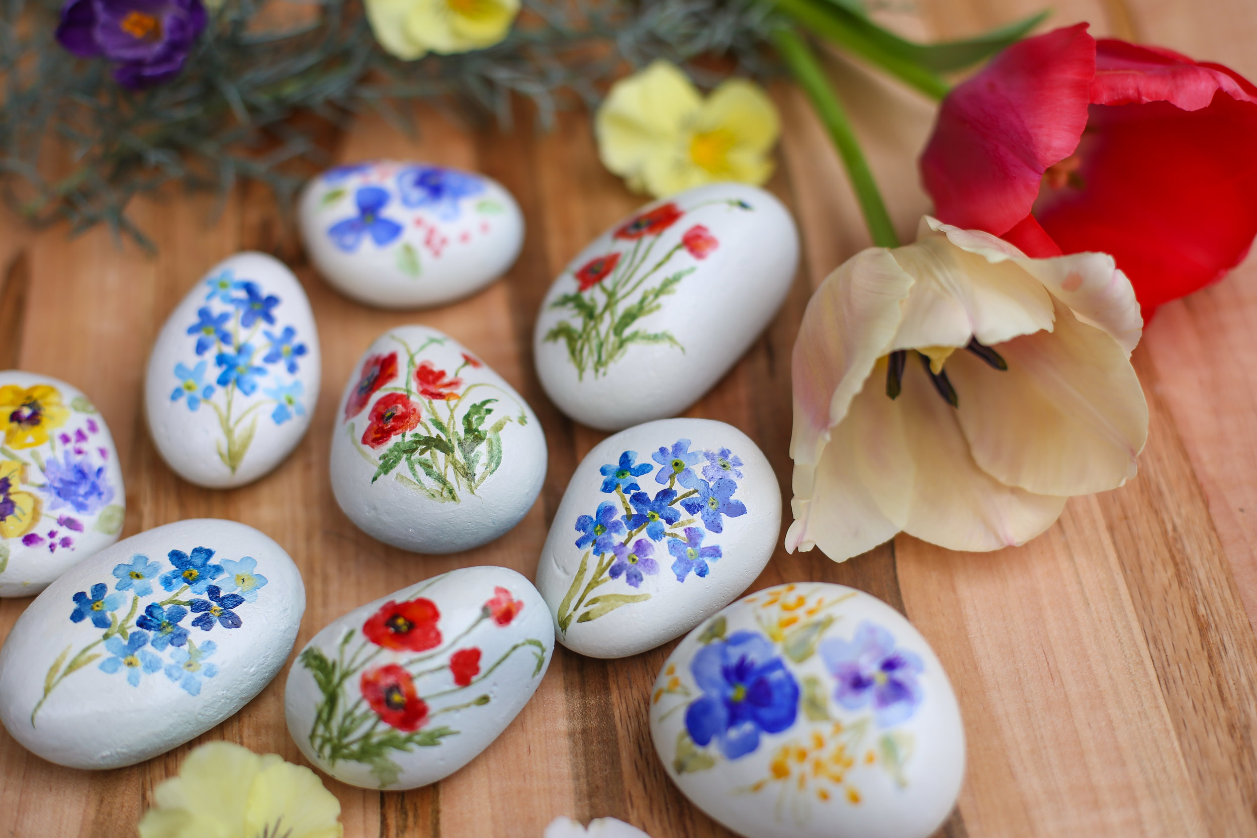 Watercolor paint on rocks, poppies, pansies, and delicate spring flowers all sealed with a shiny gloss.