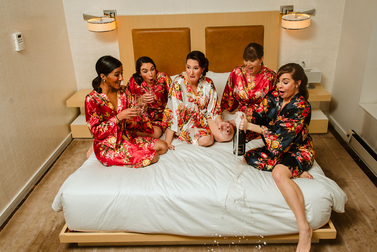 Bridesmaids open bottle of champagne