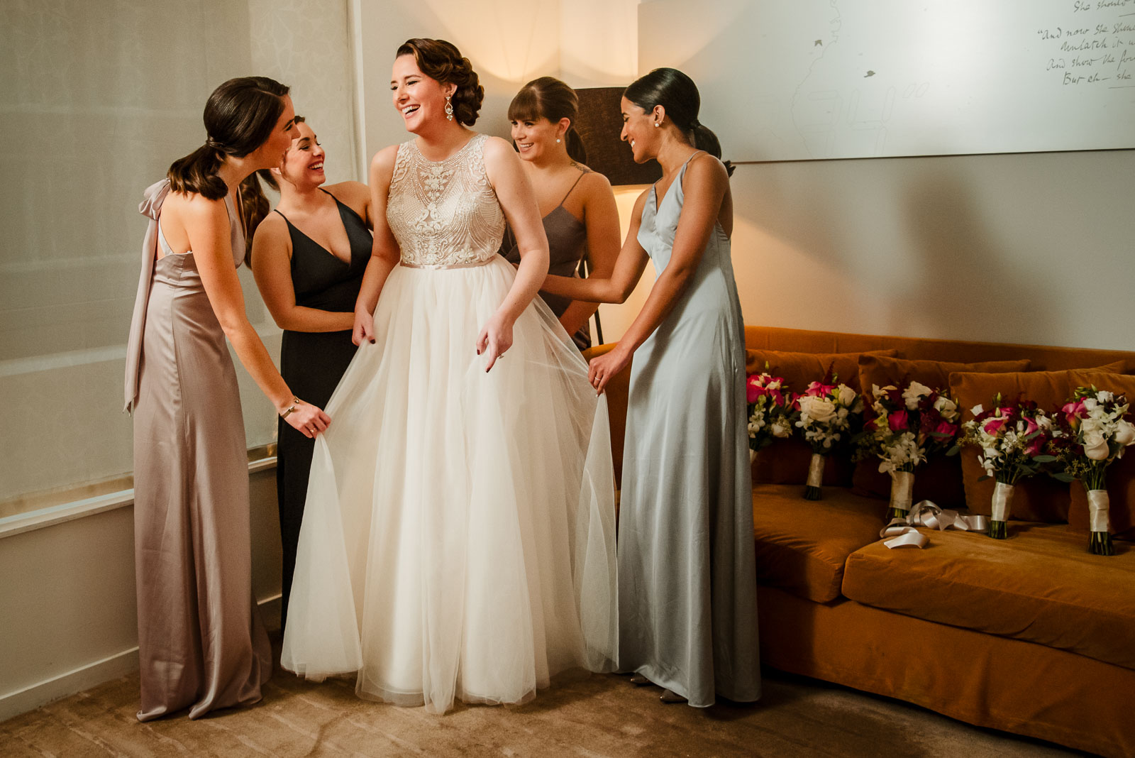 Bridesmaids help bride with her dress